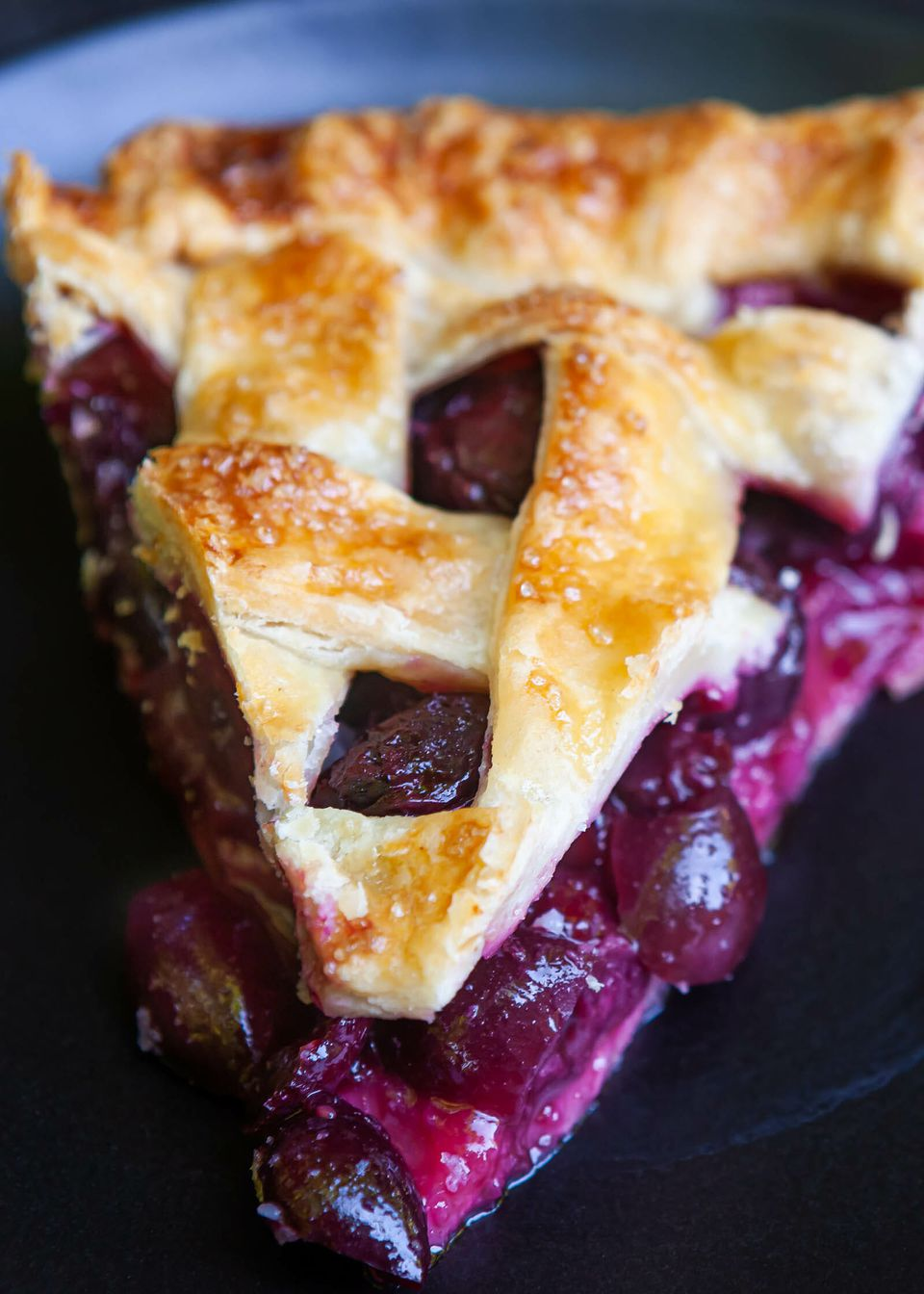Close up of the best cherry pie on a plate. The pie has a lattice crust and the cherry pie filling is visible.