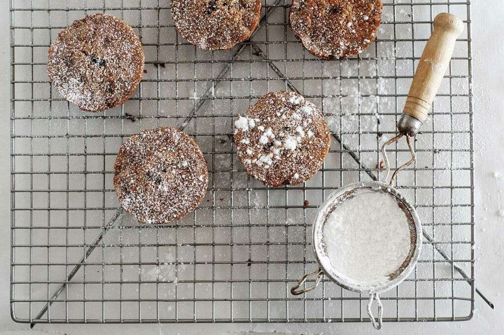Grain-Free Chocolate Olive Oil Cakes on wire rack with powdered sugar dusting
