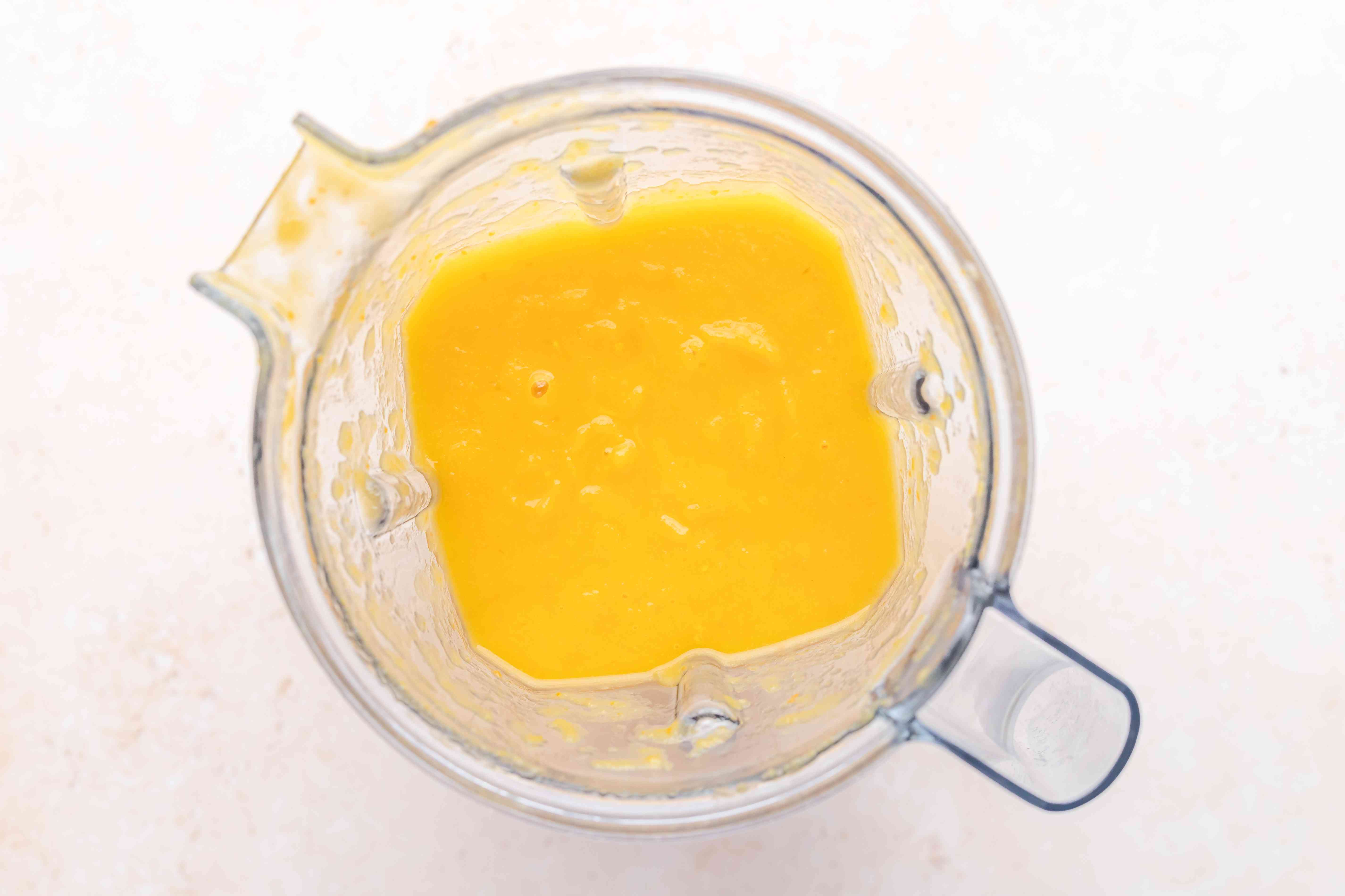 Pureed butternut squash soup in a blender.
