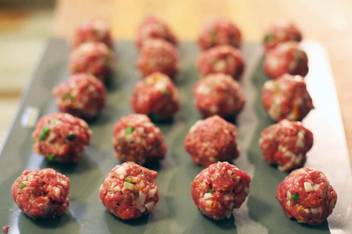 Raw greek meatballs pepared on a cooking sheet