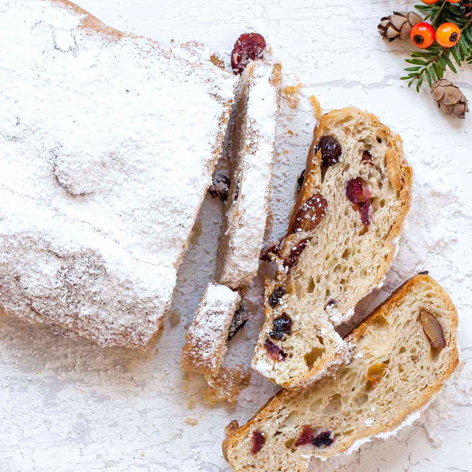 Stollen Christmas Bread filled with rum-soaked dried fruit coated with powdered sugar and sliced on a platter..