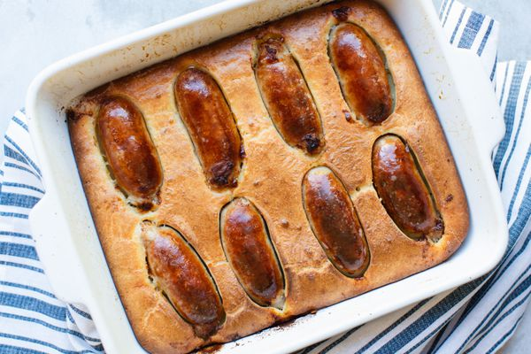 Overhead view of toad in the hole in a baking dish with a blue striped linen underneath.