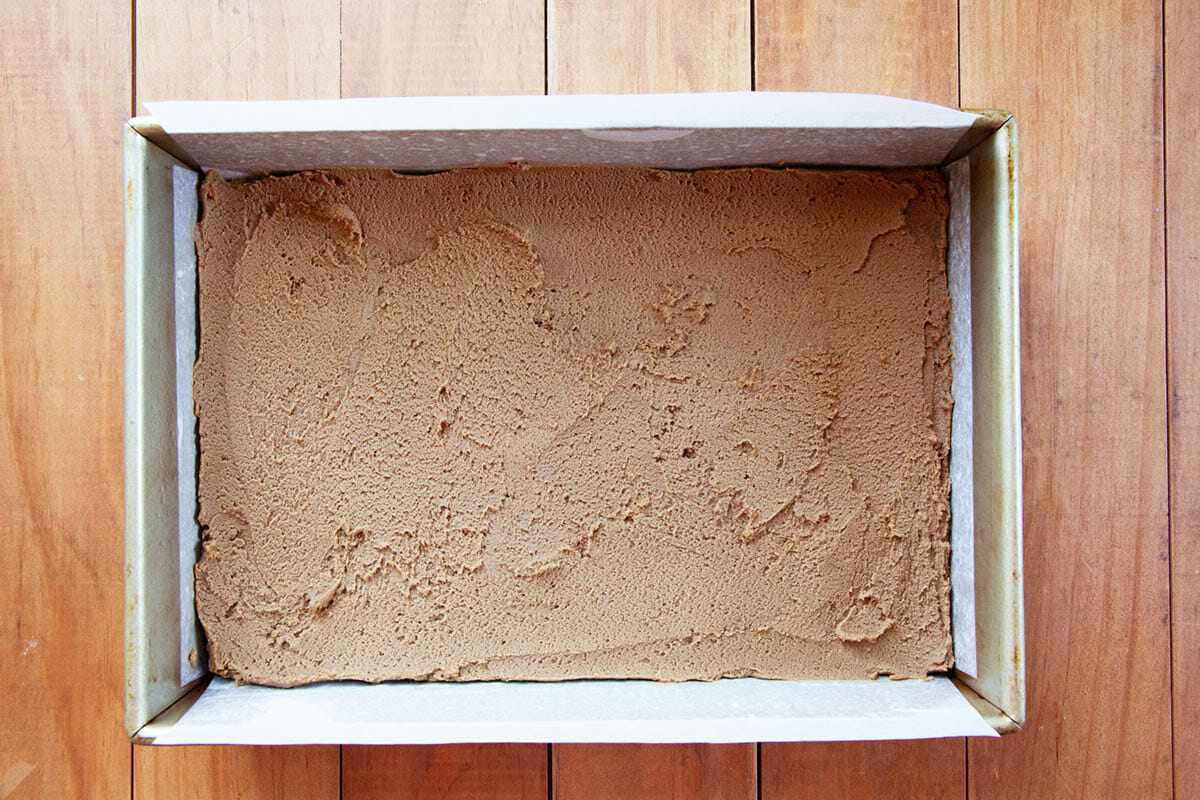 Batter spread in a parchment lined baking pan to show How to Make Gingerbread Bars.