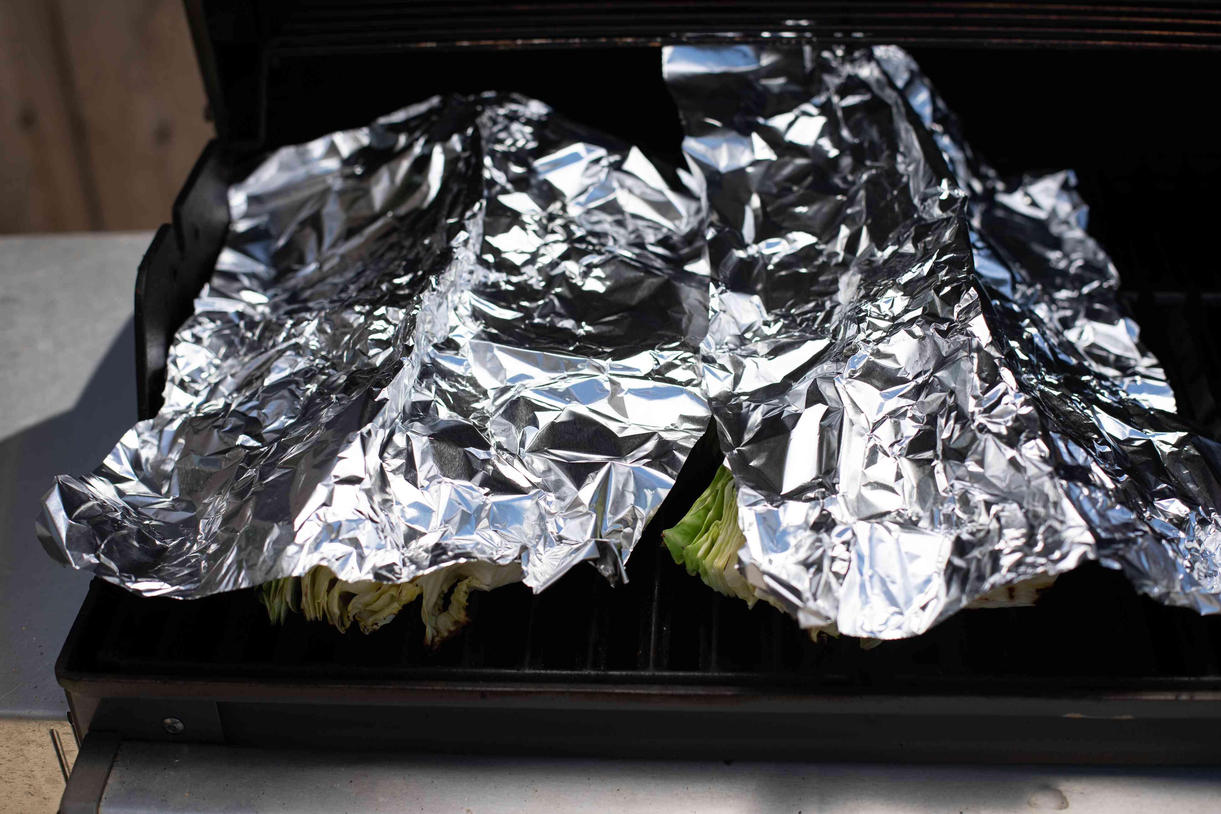 Grilled cabbage wedges covered with foil.