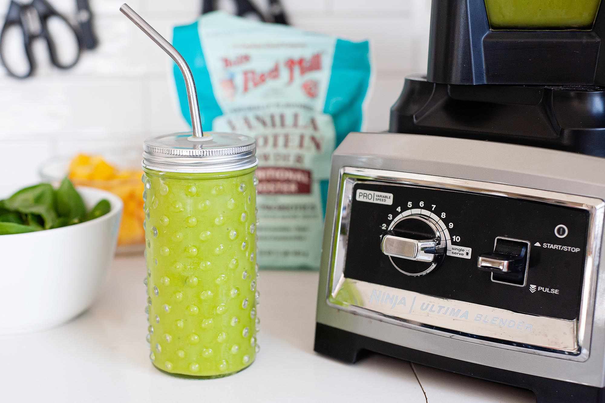 A green smoothie in a lidded glass mason jar with a stainless steel straw sits on a white countertop. The base of a high speed blender is to the right of the smoothie. A bowl of spinach, cut fruit and a bag of protein powder are to the left of the smoothie as well as behind it.