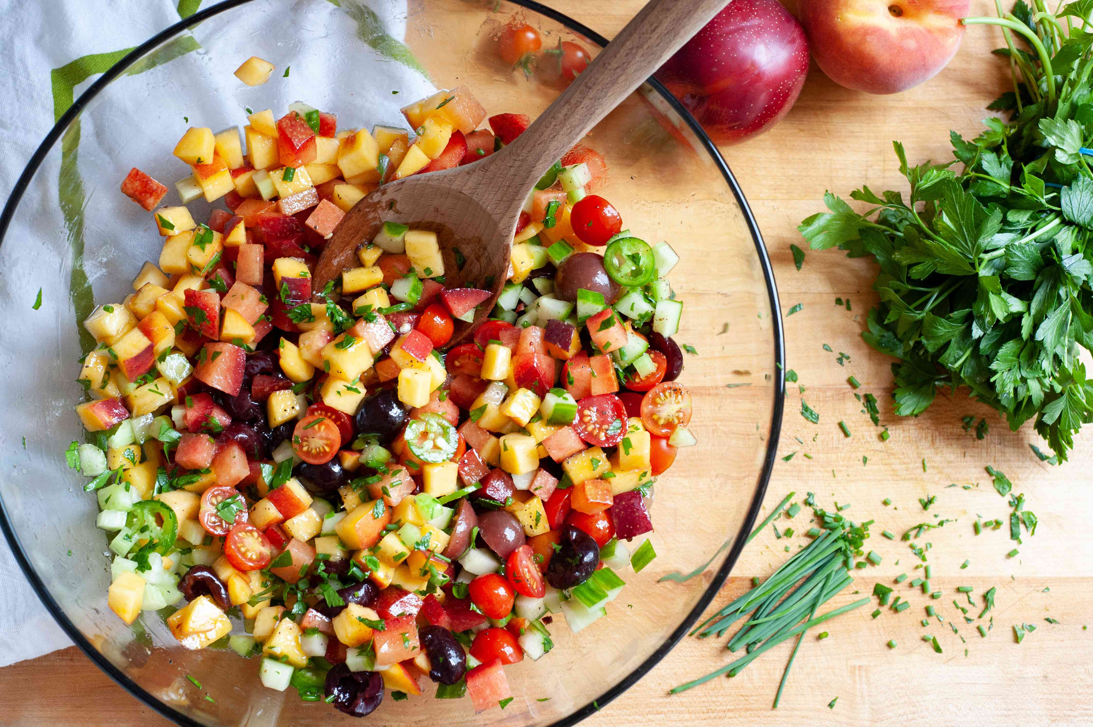 Mixing ingredients in a bowl to make a stone fruit and vegetable salad.