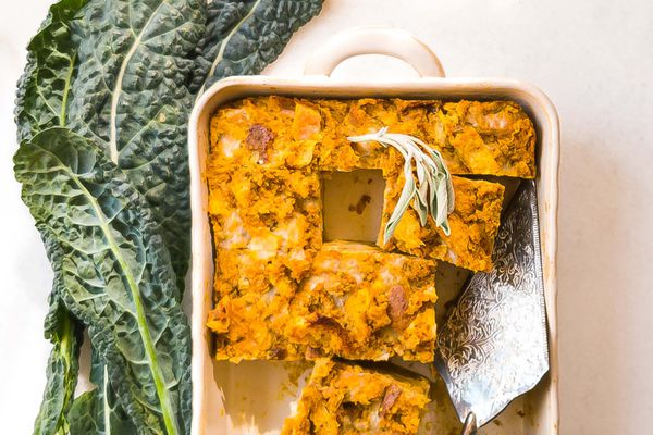 A Vegetarian Breakfast Casserole with Butternut Squash, Kale and Sage in a casserole dish with some pieces removed and a silver serving utensil in the casserole dish.