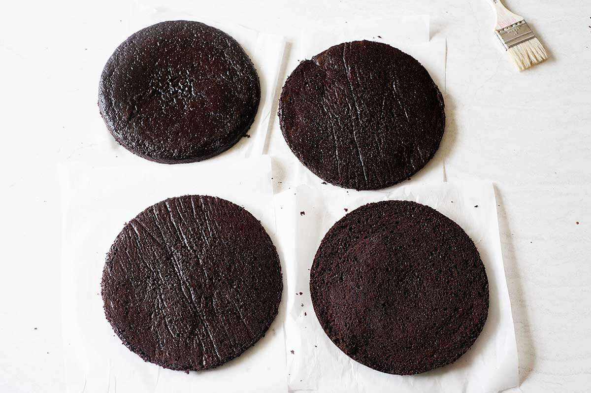 Four cake rounds set on parchment paper to make Homemade Black Forest Cake.