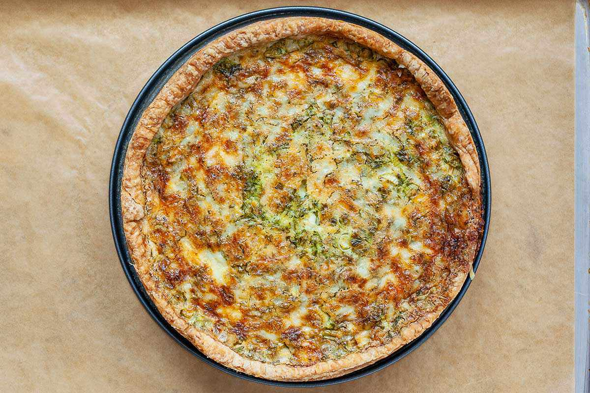 An Easter quiche baked in a springform pan and cooling on baking sheet covered in parchment paper.