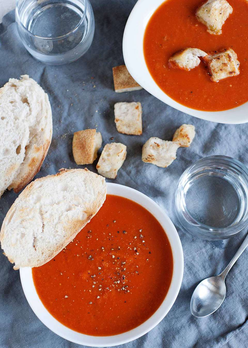 Easy Homemade Tomato Soup - tomato soup in a white bowl with a piece of bread, and pieces of bread crumbs on the table cloth