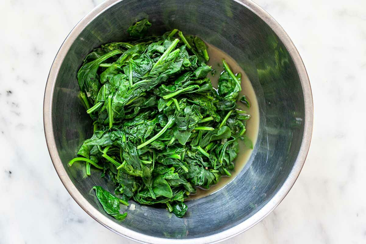 Sauteed spinach in a metal bowl for Easy Creamed Spinach.
