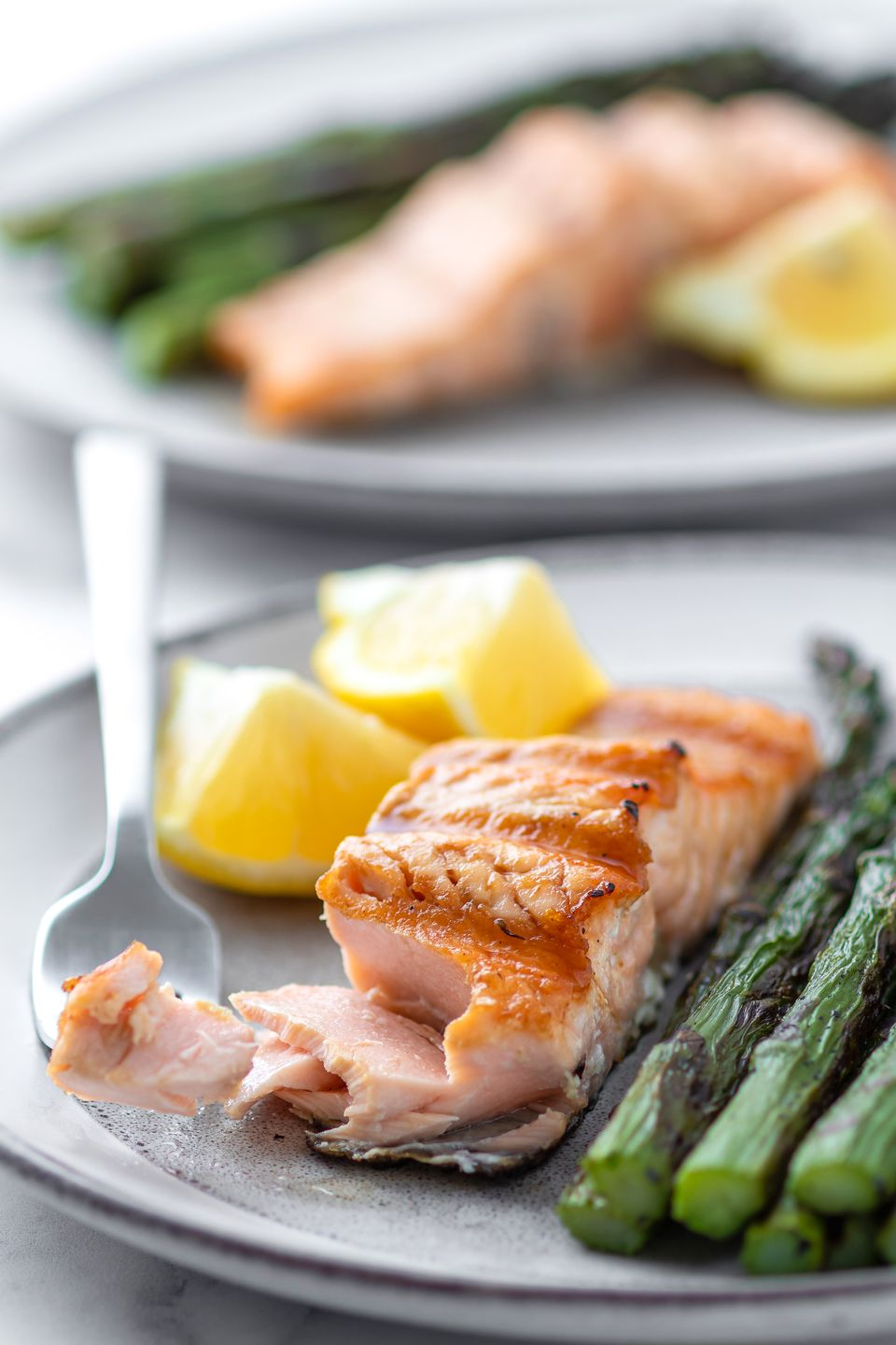 Grilled salmon on a plate with asparagus and a second plate behind it.