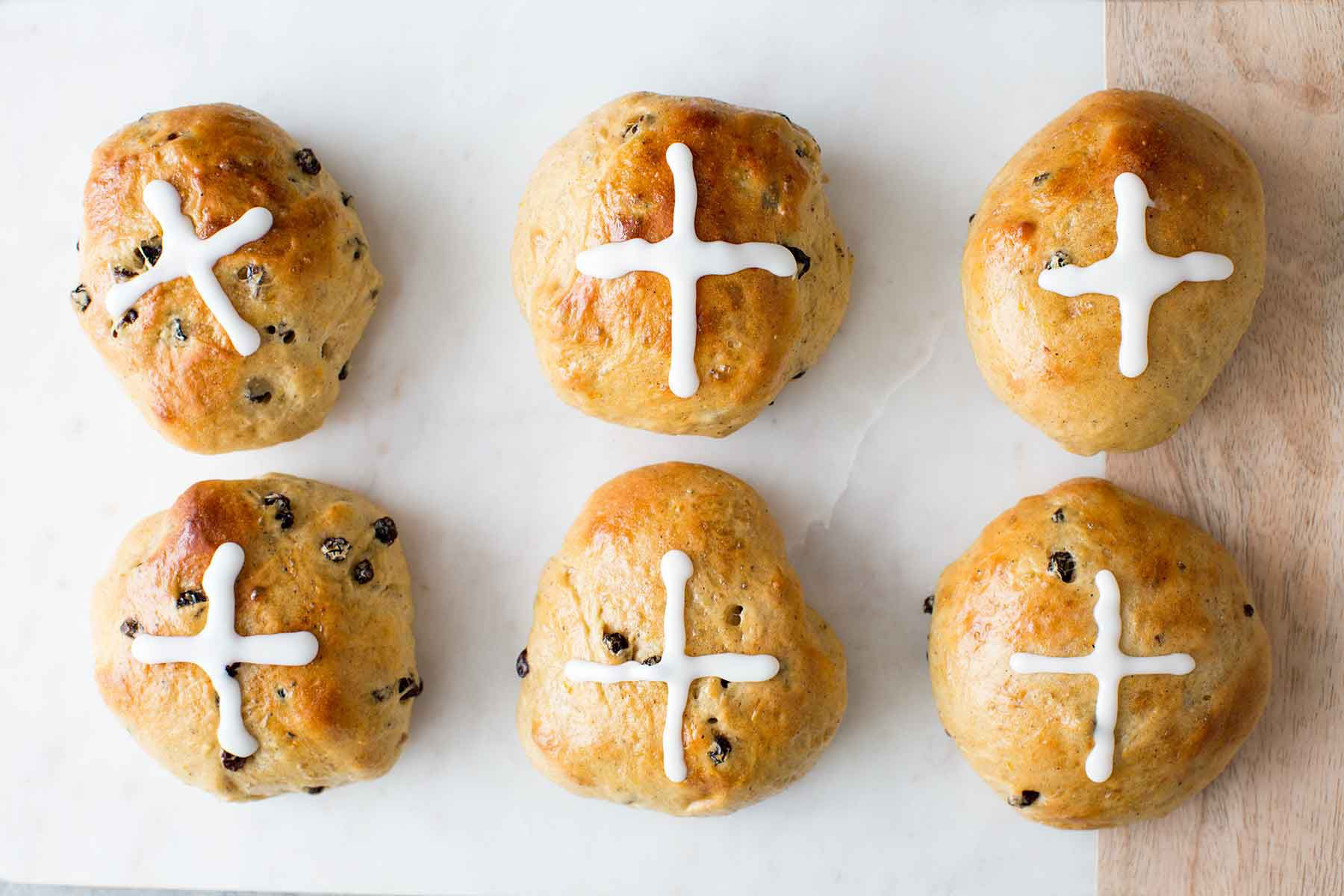 Homemade Hot Cross Buns on a surface with sugar crosses piped on top