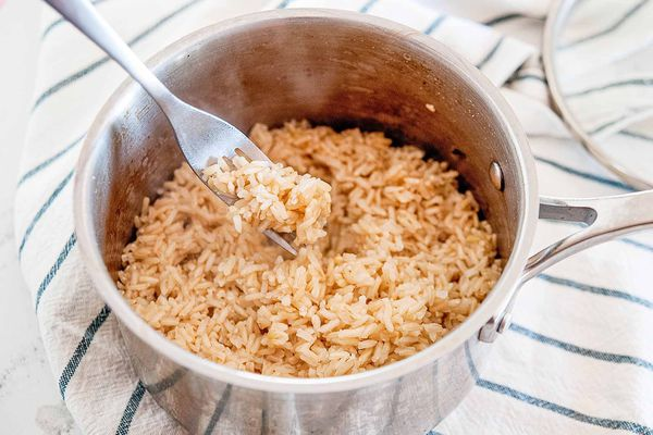 Pot with fork fluffing long grain brown rice that was cooked on a stovetop