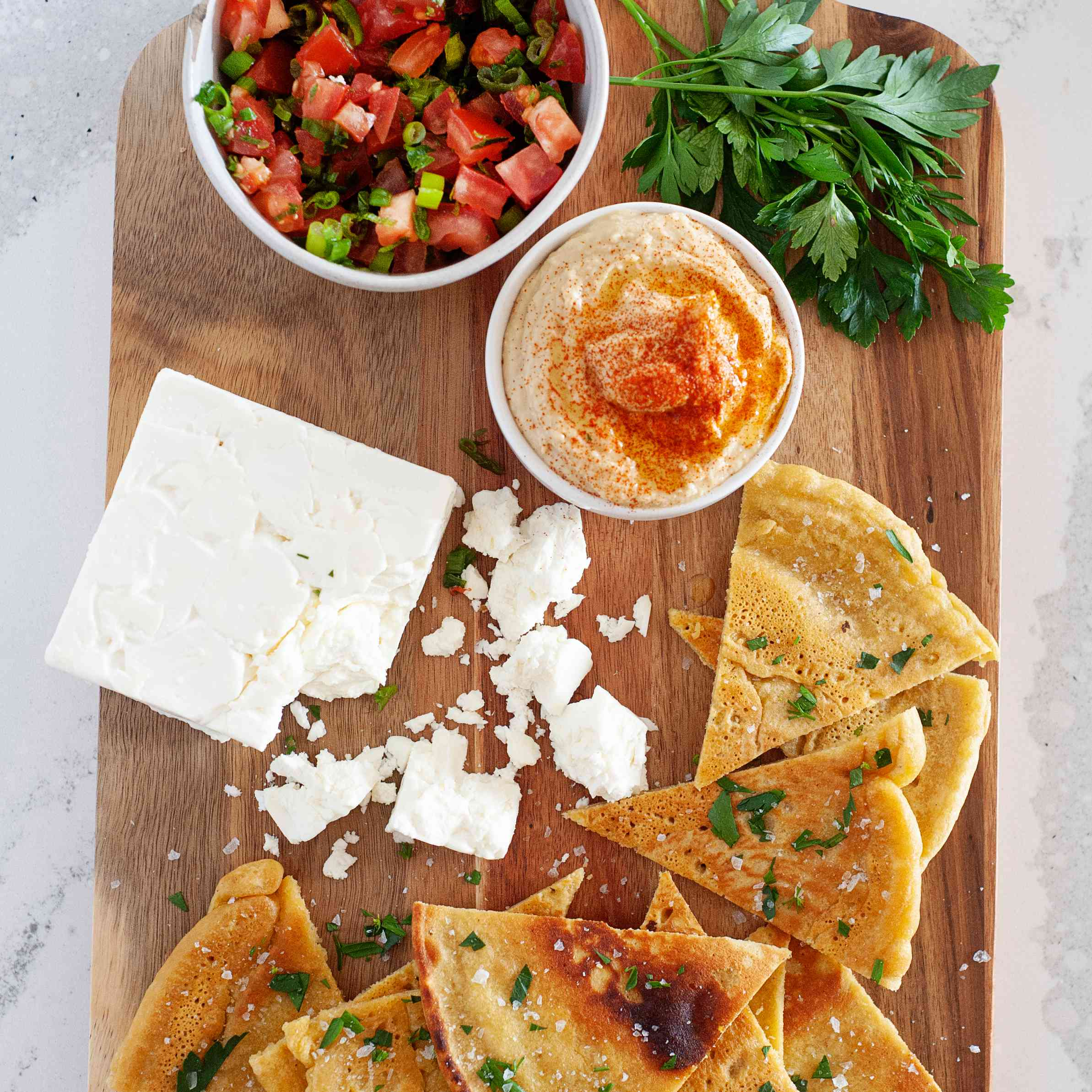 Socca—Gluten-Free Chickpea Flour Flatbread cut into triangles and served with a variety of sauces, vegetables, and cheese.