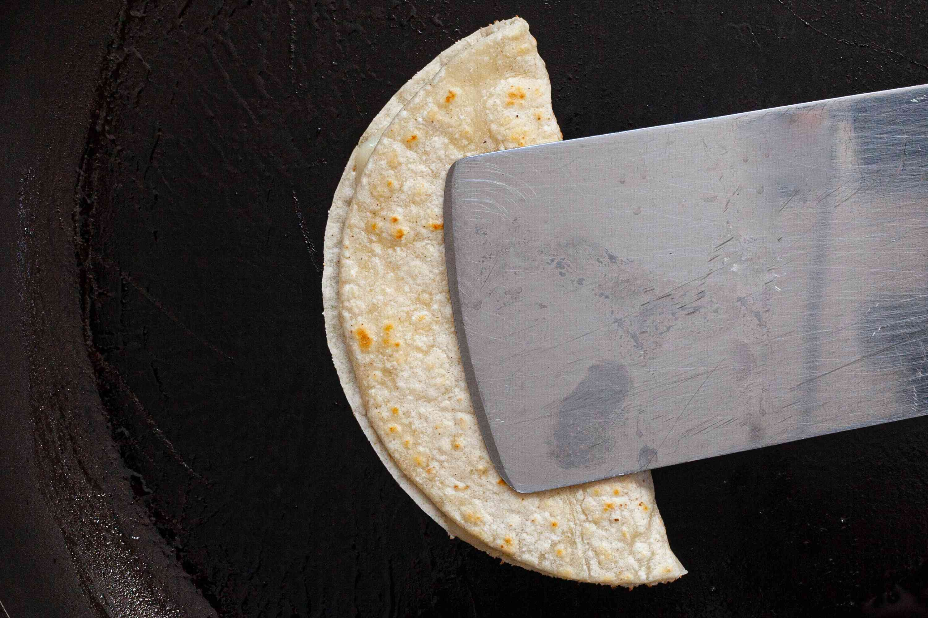 A tortilla pressed in half on a skillet to make a vegetarian tacos recipe.