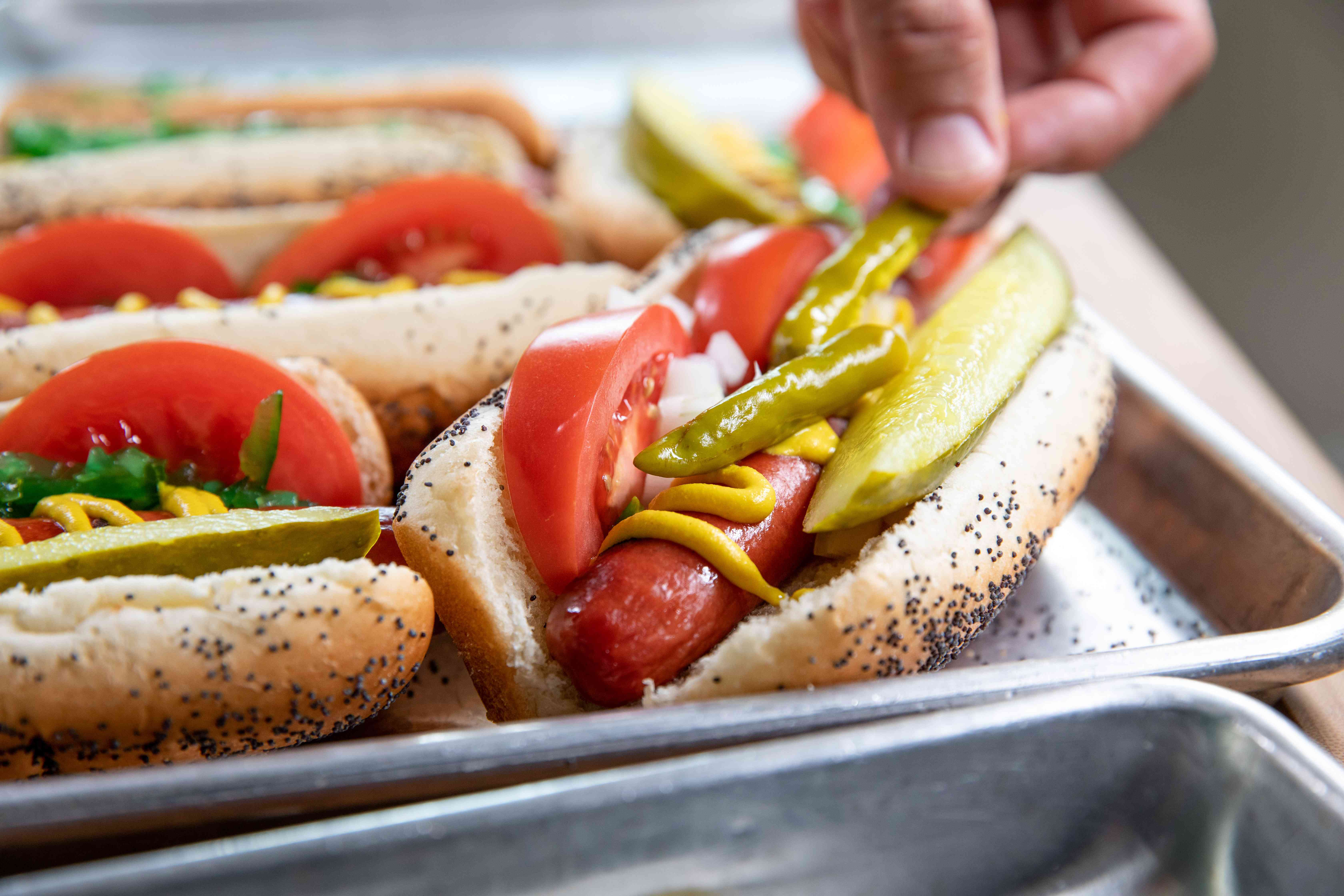 Adding tomatoes, pickles, and sport peppers to make Chicago-style hot dogs.