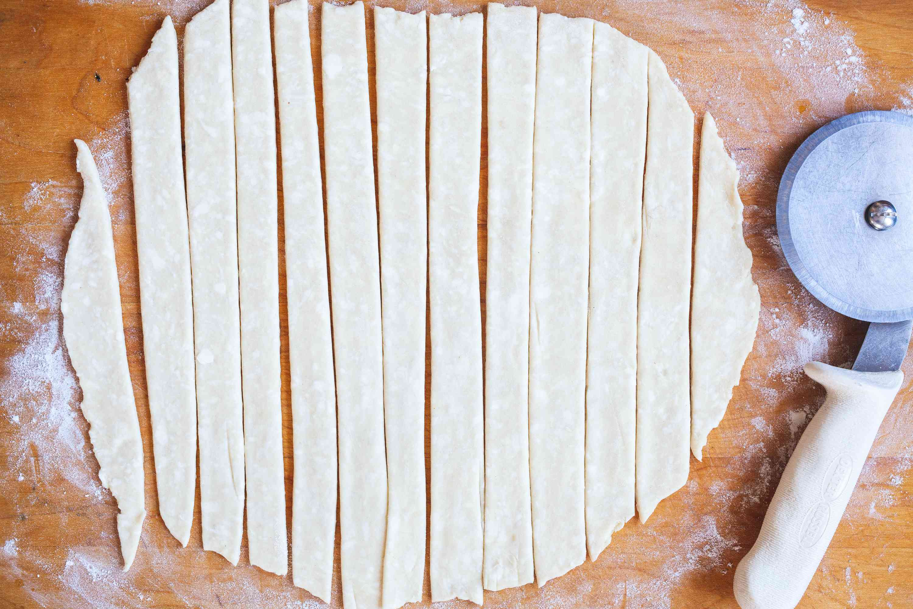 Cutting a pie crust into strips to show how to make a lattice crust.