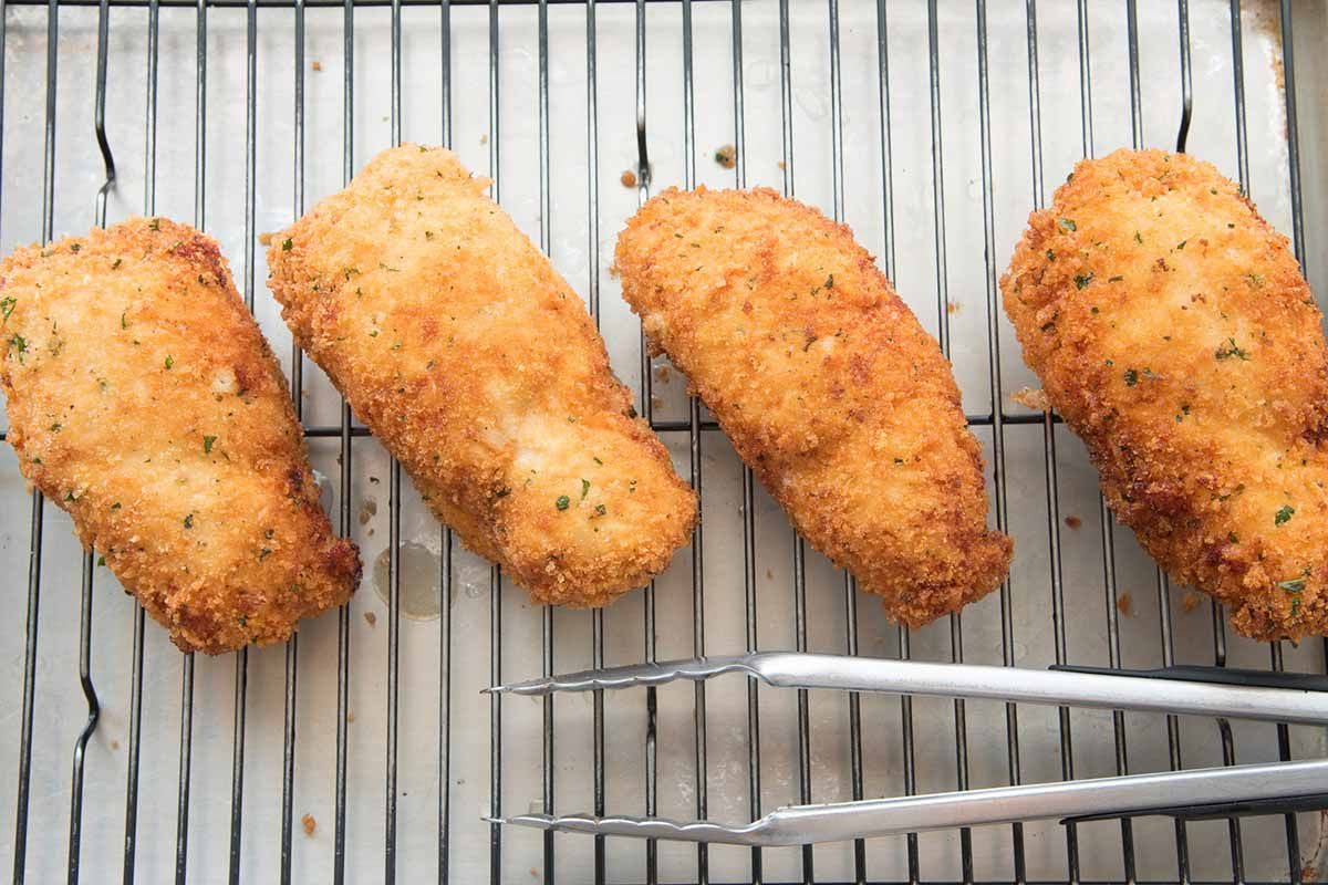 Breaded and fried chicken cordon bleu on a a bakers cooking rack.