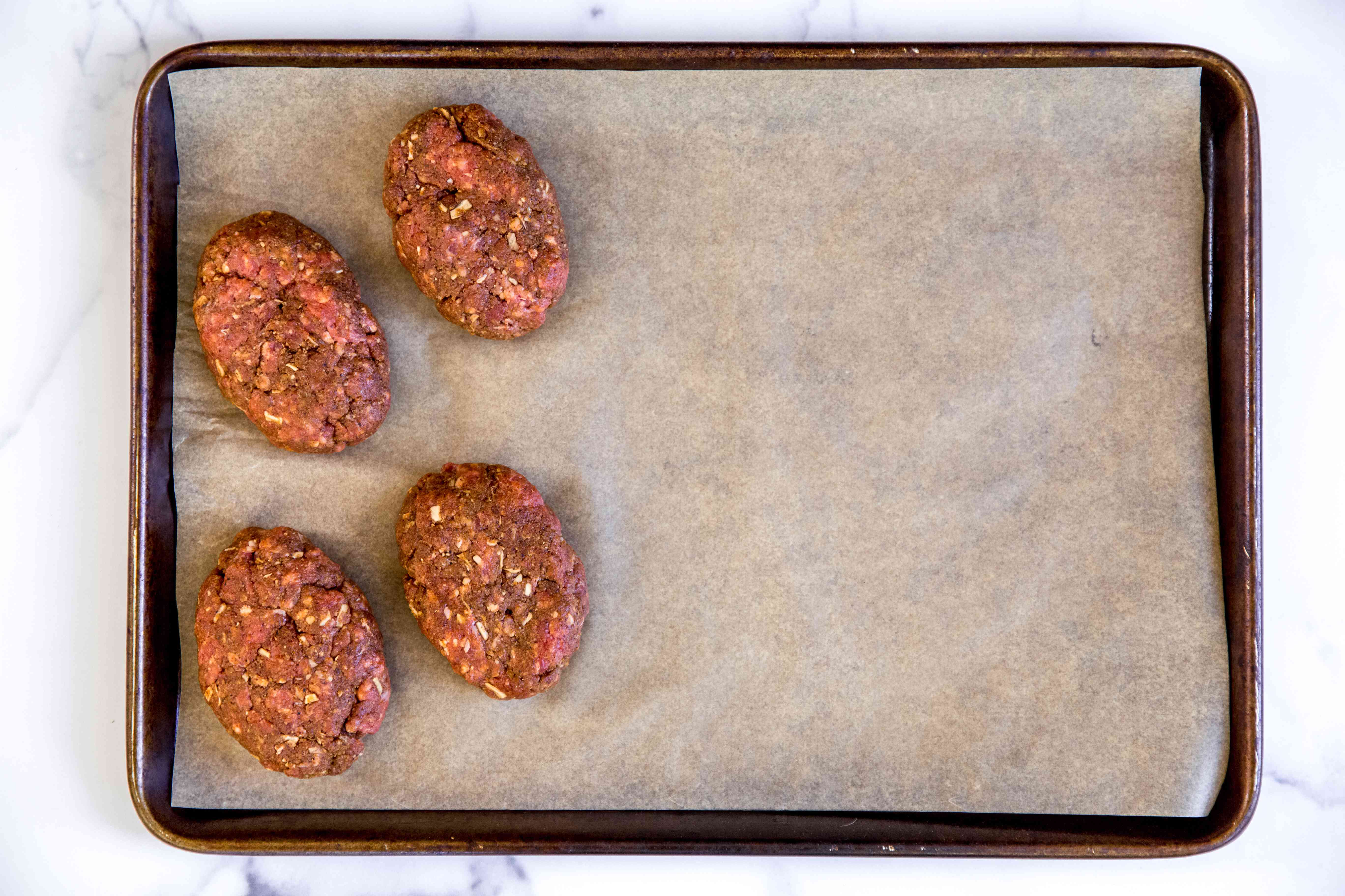 Sheet pan with mini meatloaves ready to be baked.
