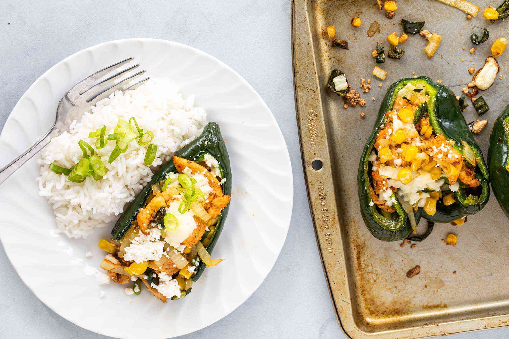 Chicken stuffed peppers on a plate with a side of rice. A baking sheet with additional peppers is to the right.