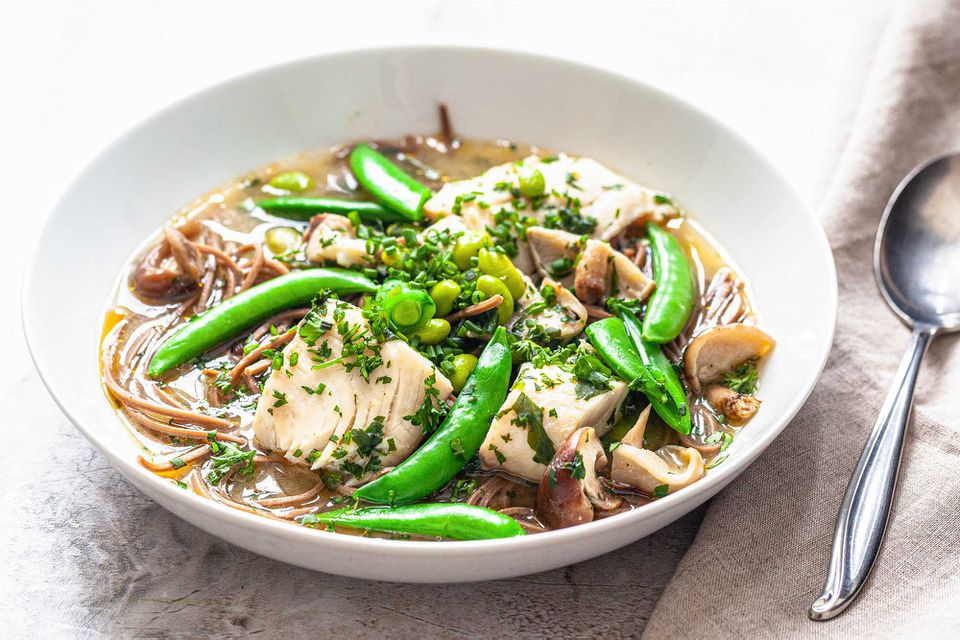 Quick Miso Soup with fish, peas, herbs and soba noodles in a white bowl on a marble background.