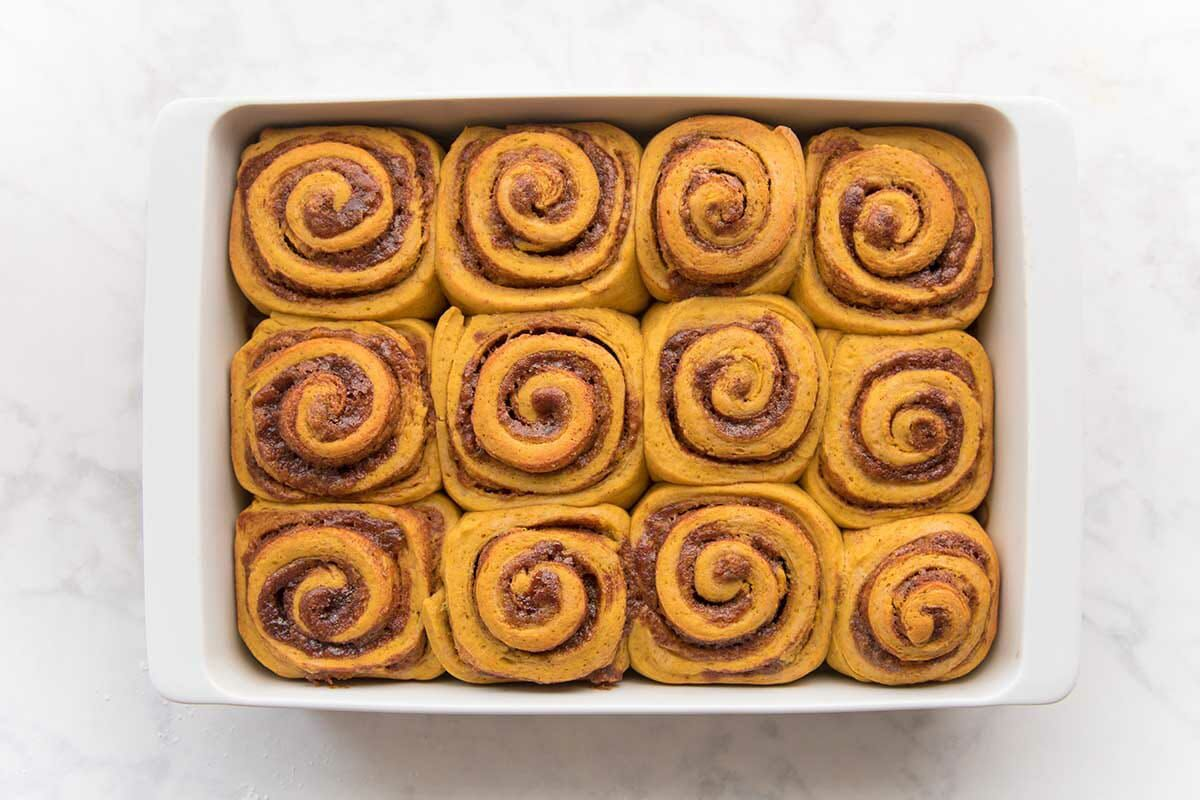 Baked cinnamon rolls in a baking dish to show how to make Pumpkin Cinnamon Rolls.