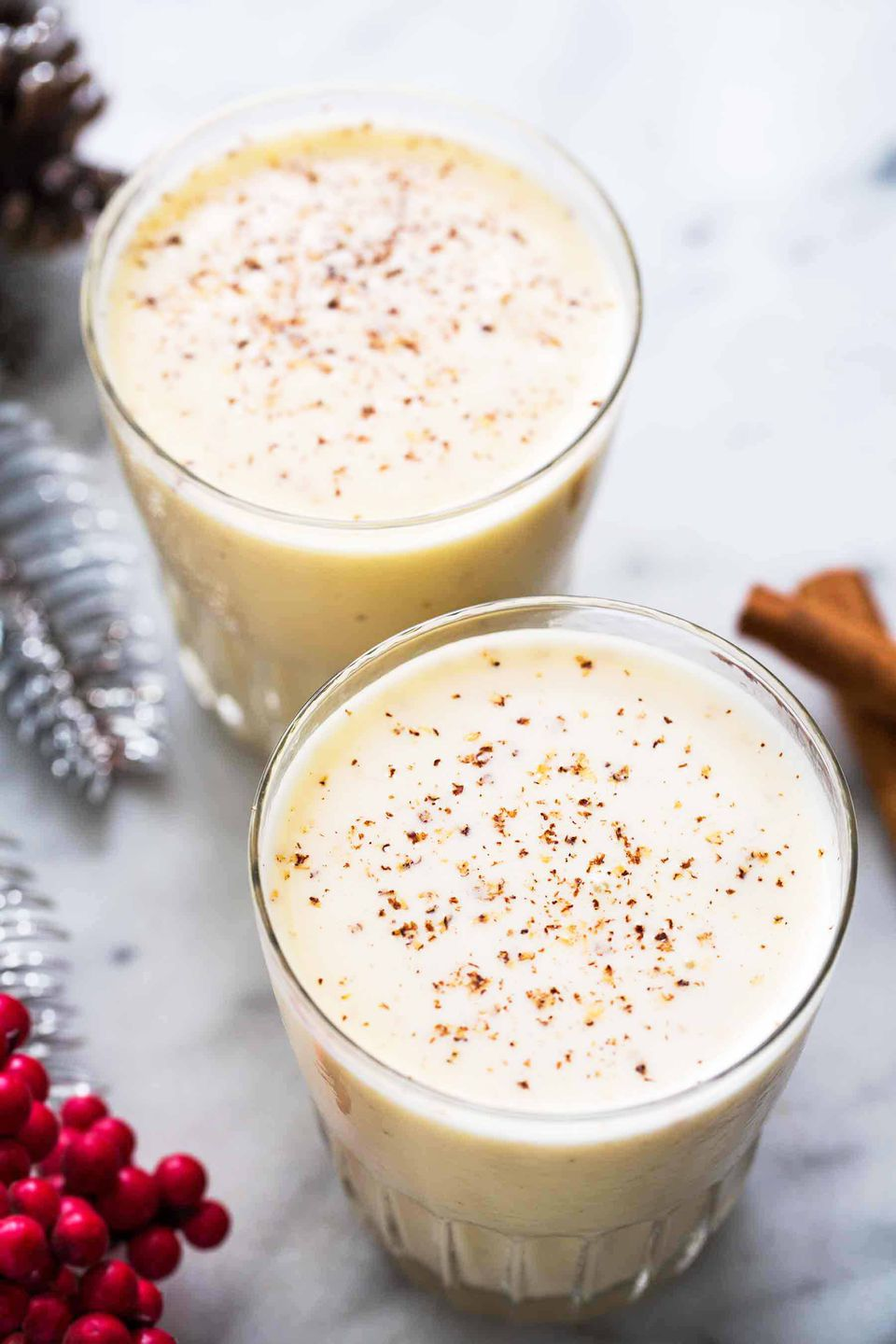 Homemade eggnog served in two glasses with nutmeg sprinkled over top