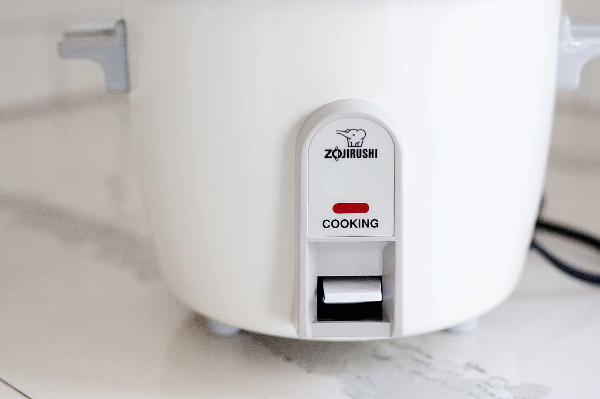 Horizontal image of a side view of the bottom half of a Zojirushi rice cooker on a white countertop.