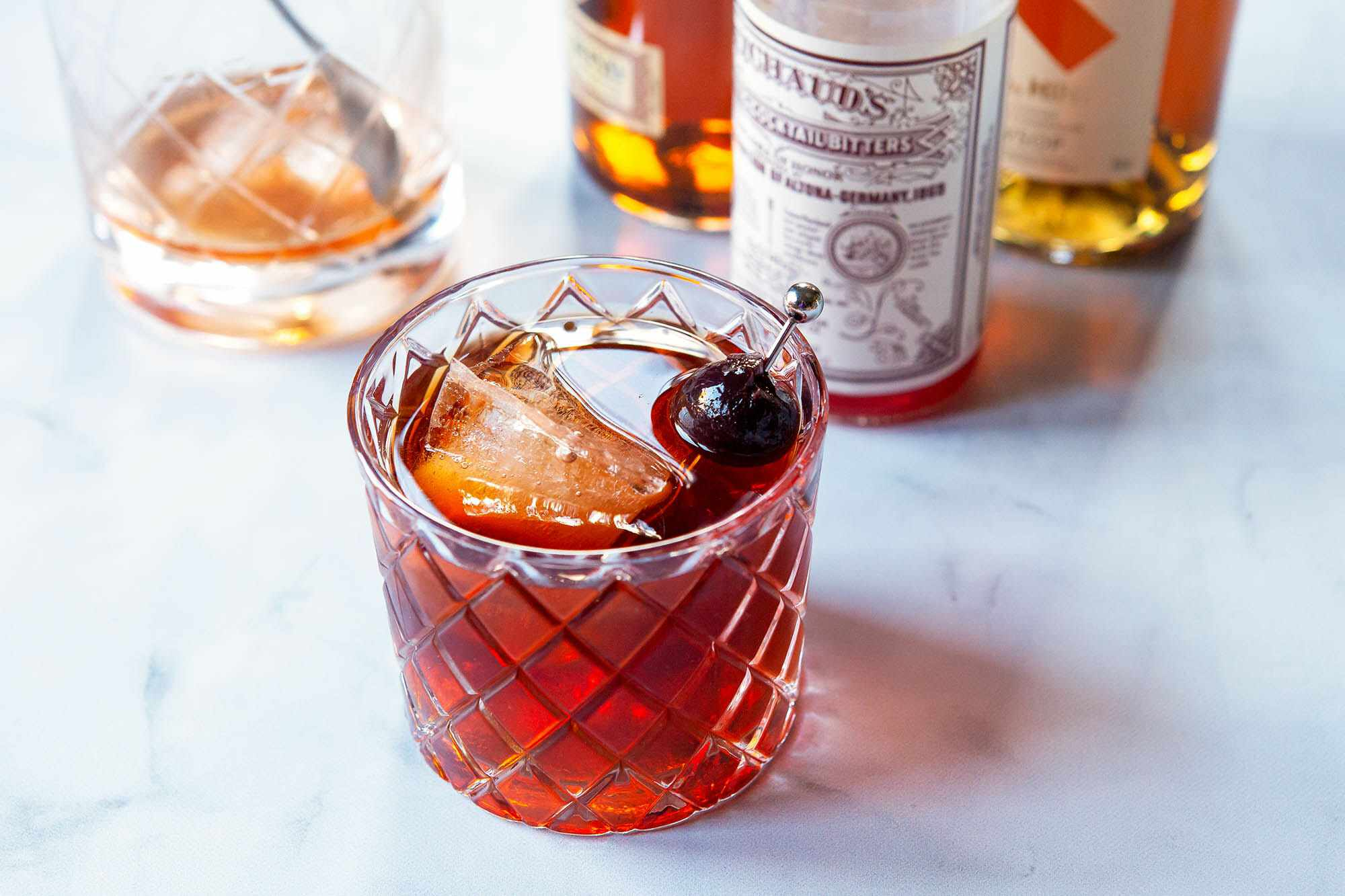 Vieux carre in a whiskey glass with ingredients to make the cocktail behind it.