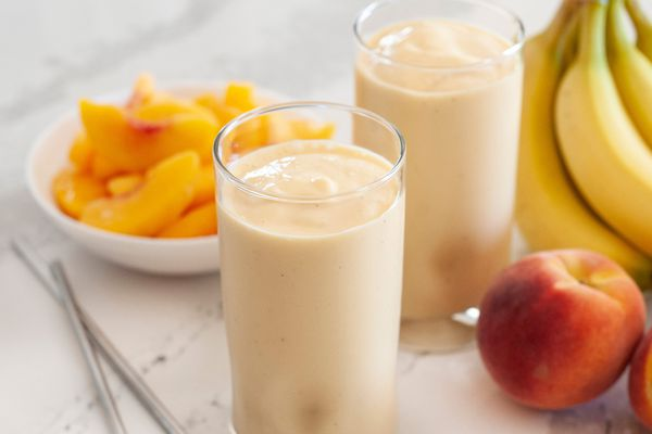 Two peach almond smoothies with whole bananas, peaches, and a plate of sliced peaches set around the smoothies.