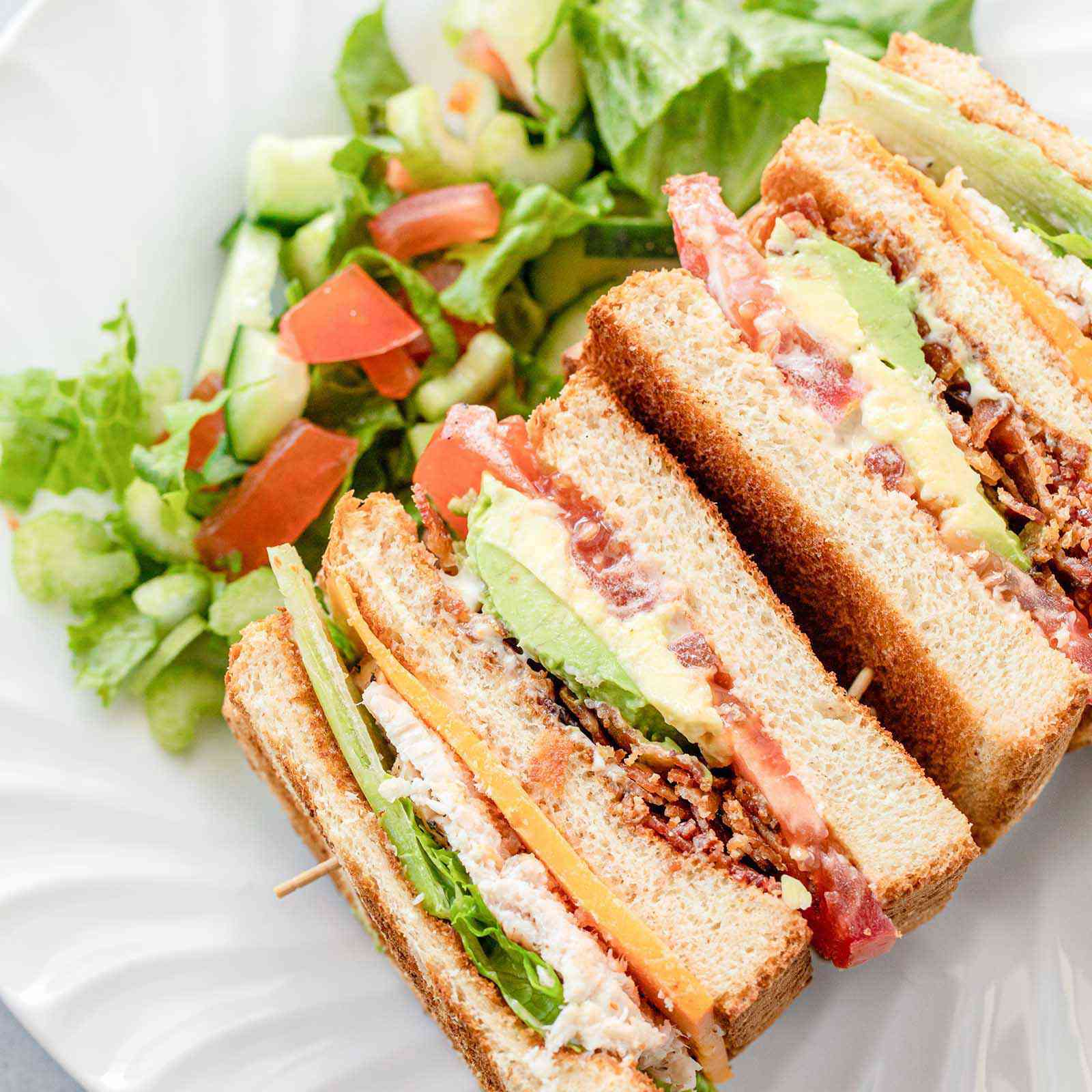 Overhead view of a turkey club sandwich on its side. A lettuce salad with cucumber and tomato is on the plate behind the sandwich.