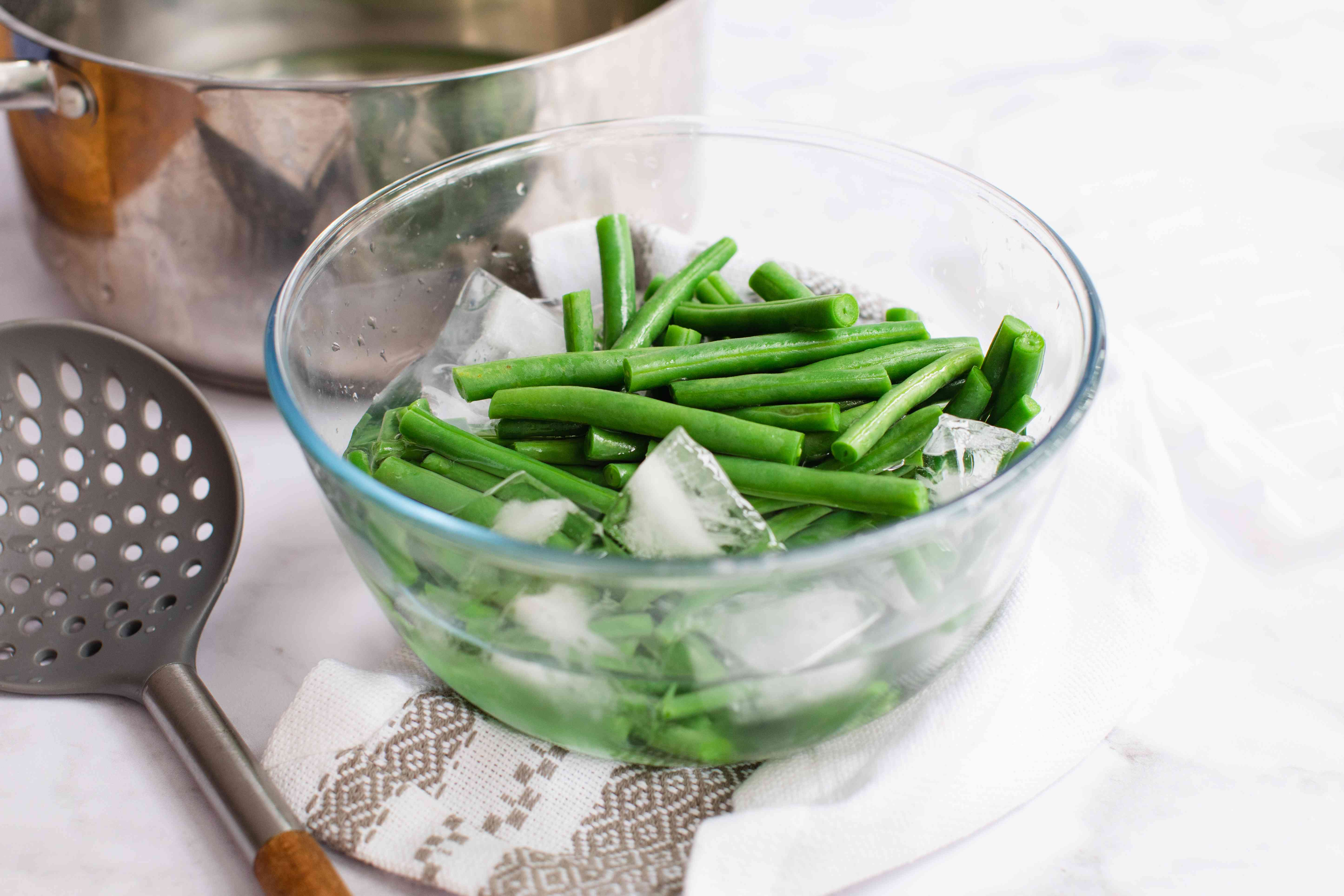 Blanched green beans in a bowl of ice for a green bean salad recipe.