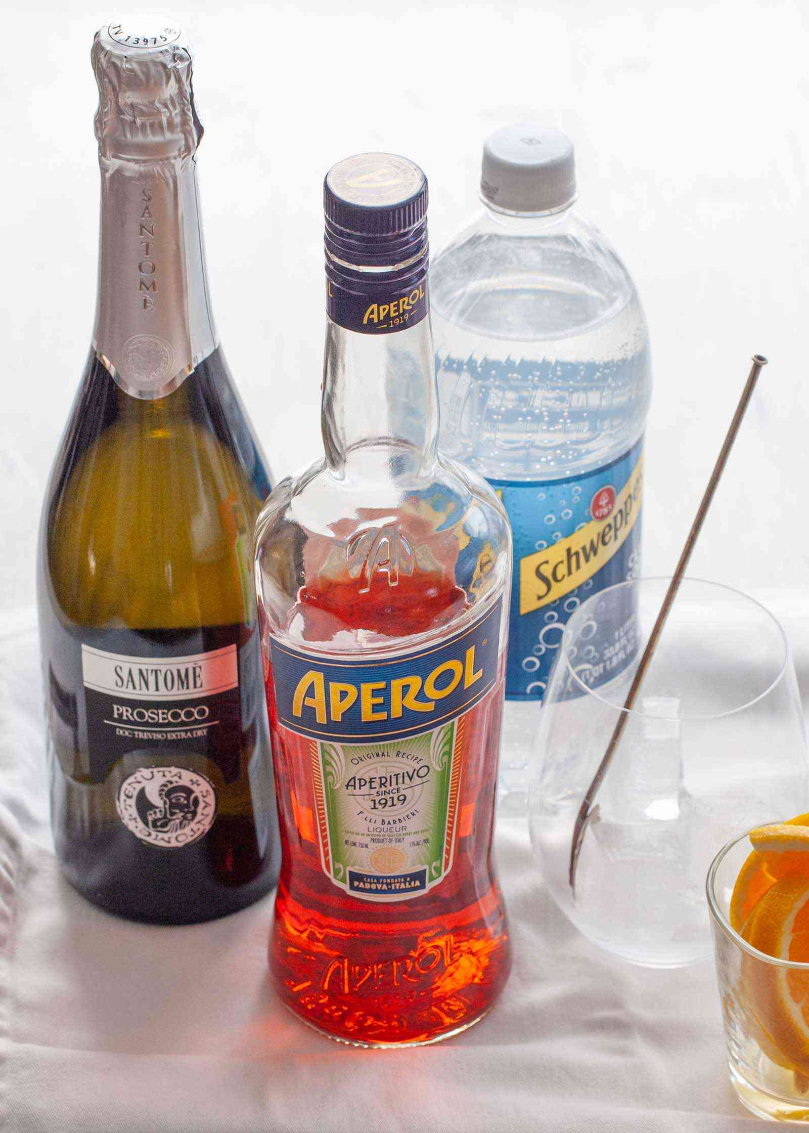 aperol spritz ingredients on a table. A bottle of aperol, prosecco, club soda and a glass with a stir stick and ice inside. A small glass of sliced oranges is in the lower right corner.