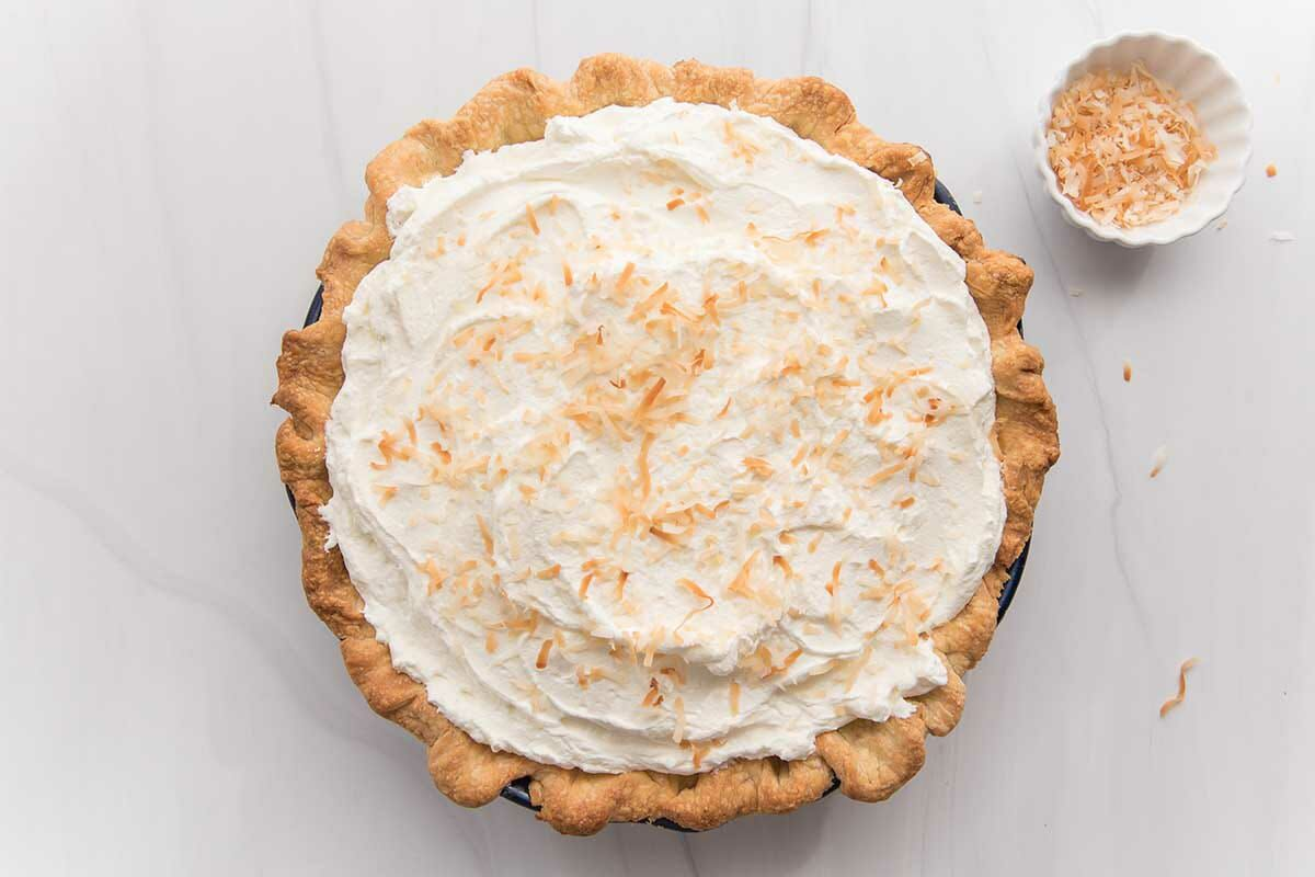 Overhead view of a homemade coconut cream pie with a small container of toasted coconut to the right.