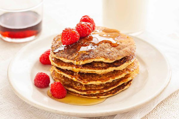 Healthy oatmeal pancakes stacked high on a whie plate drizzeled with maple syrup and topped with raspberries.