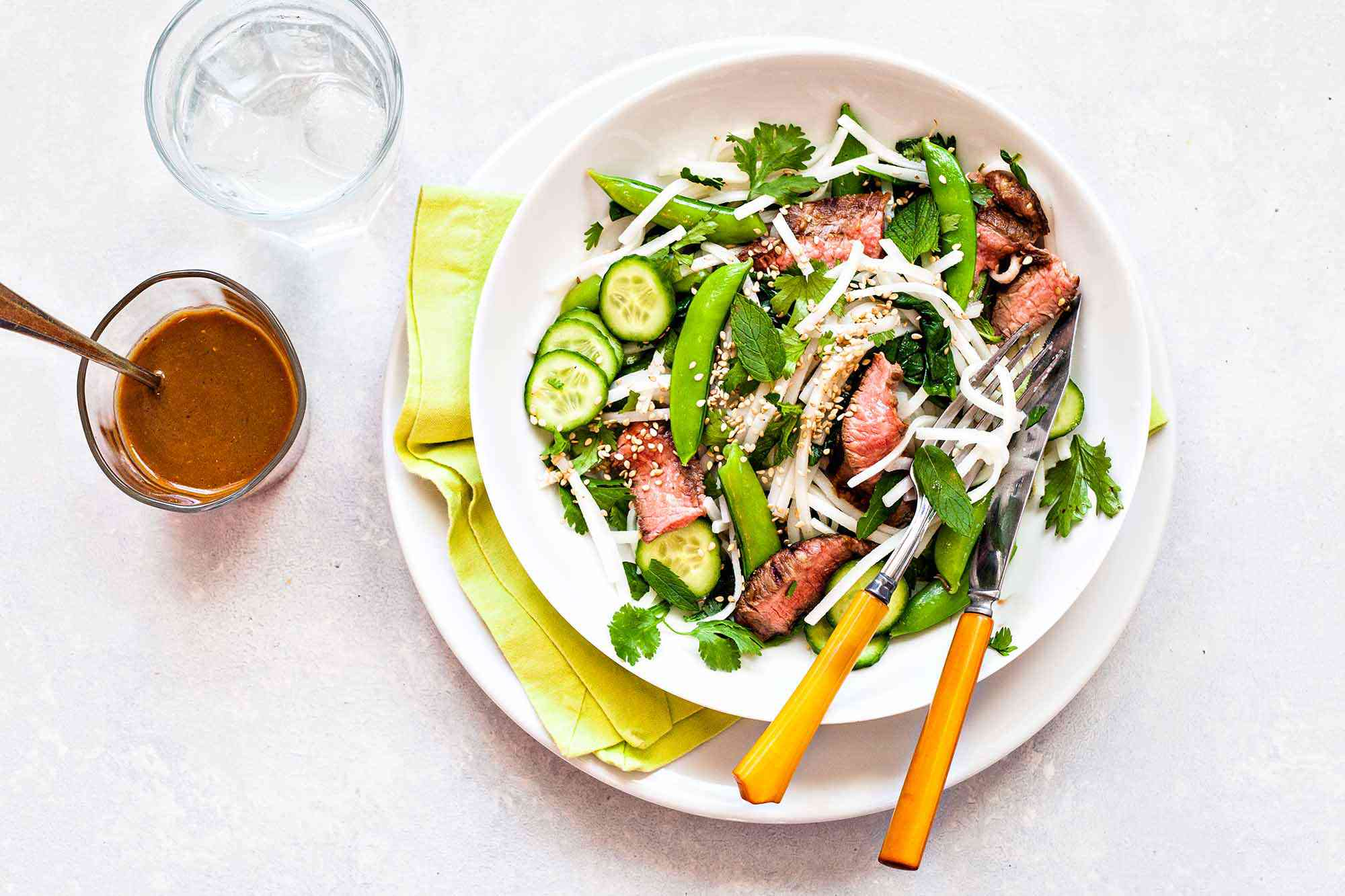 Noodles with Steak, Vegetables and Lime Dressing - noodle salad with beef and vegtables in a white bowl
