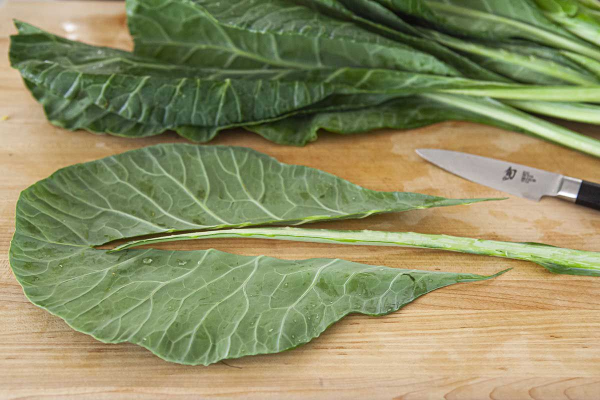 Prepare collard greens by trimming out the stem