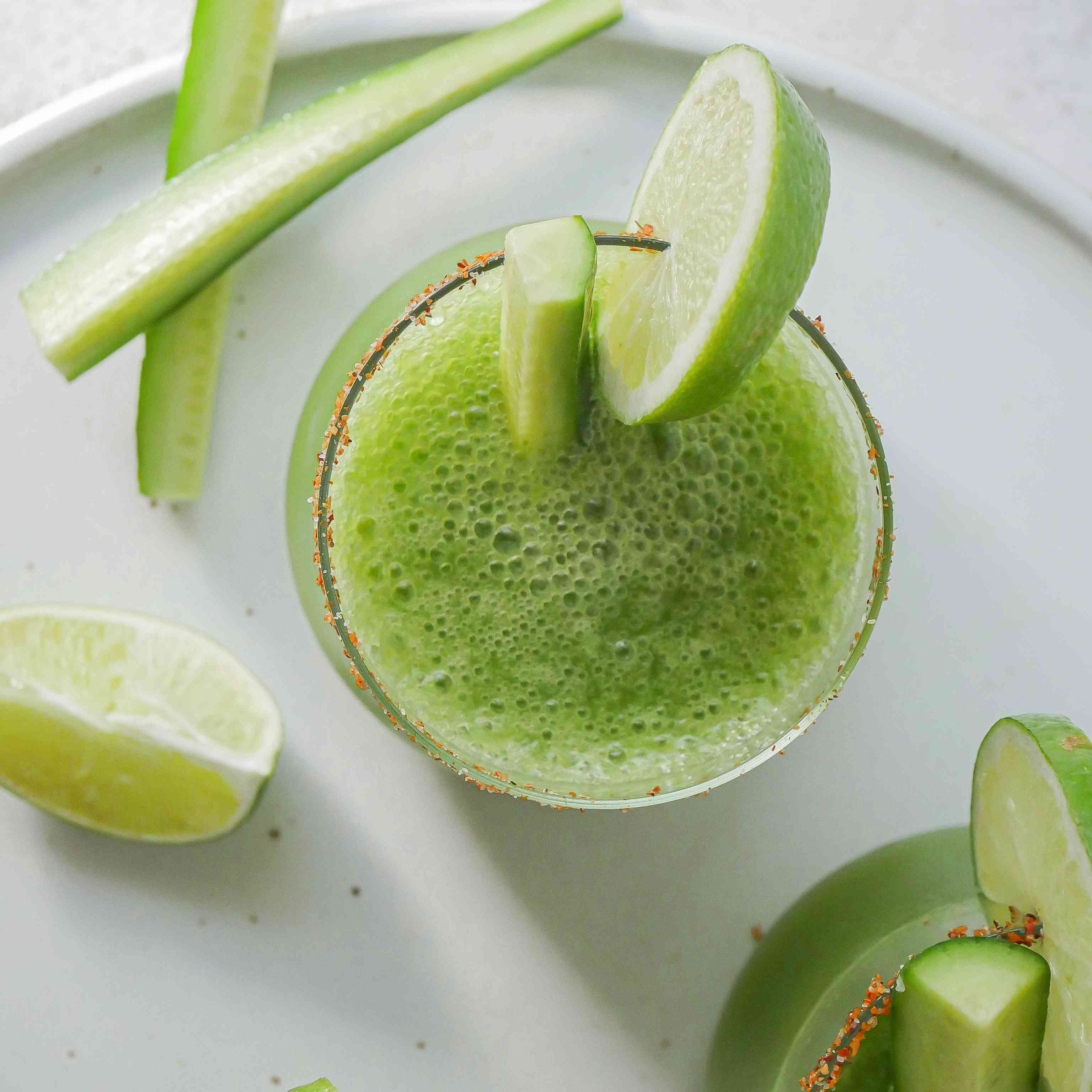 Overhead view of a Cucumber margarita garnished with cucumber and lime.