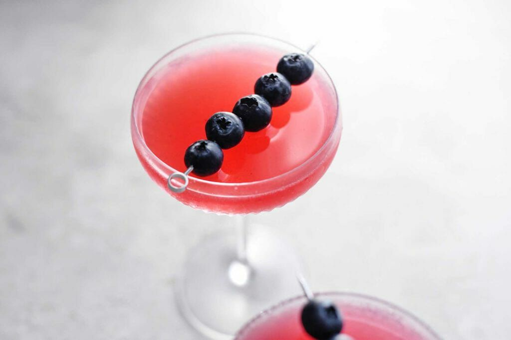 Cosmopolitan Drink with Blueberry red cocktail with blueberry garnish