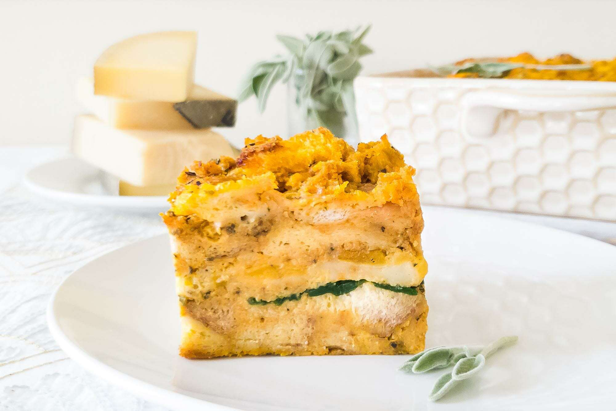 Side view of the layers of a Pumpkin Sage Strata on a white plate with a casserole dish, cheese wedges and sage behind it.