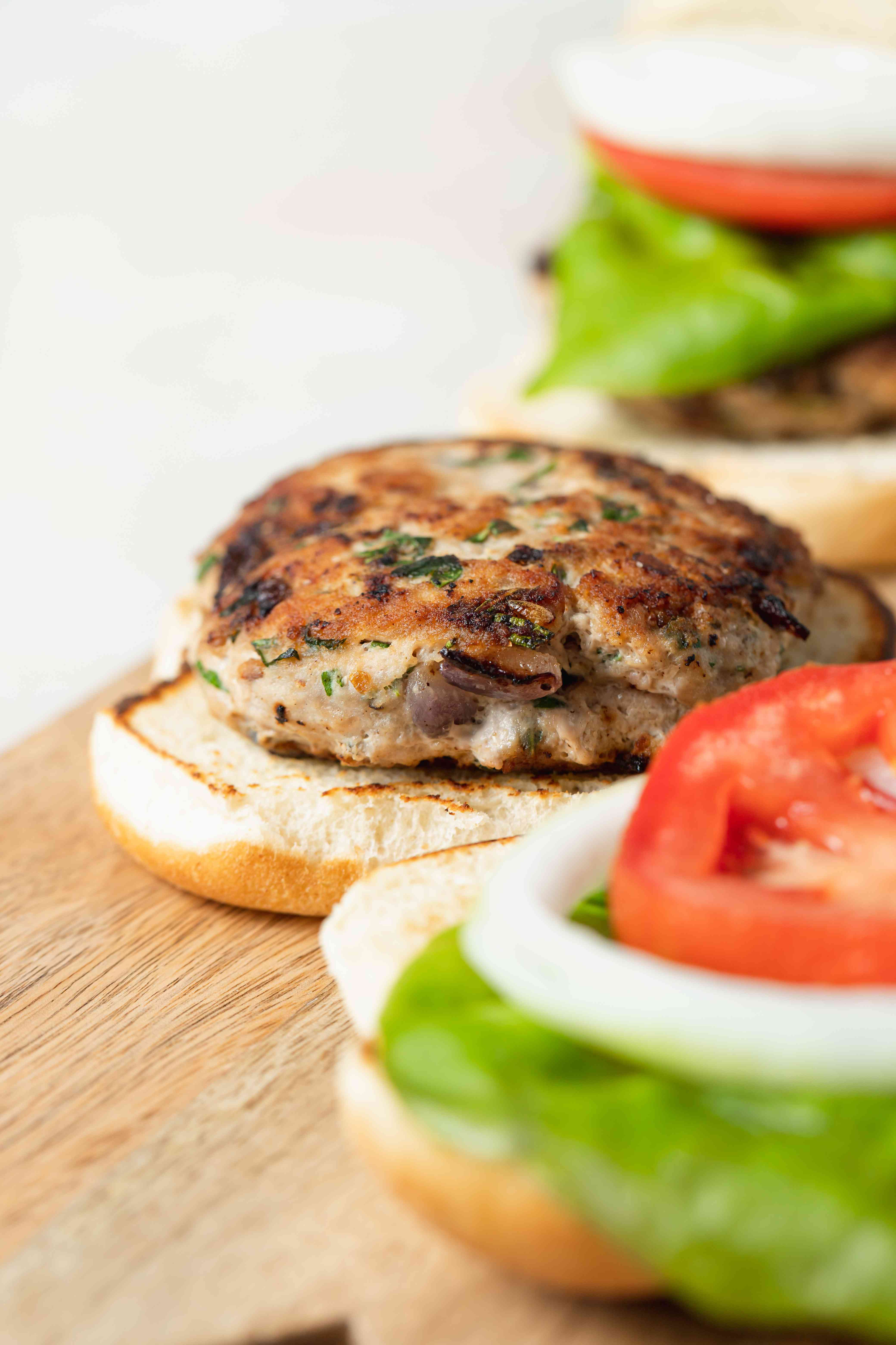 Side view close up of partially assembled turkey burgers.