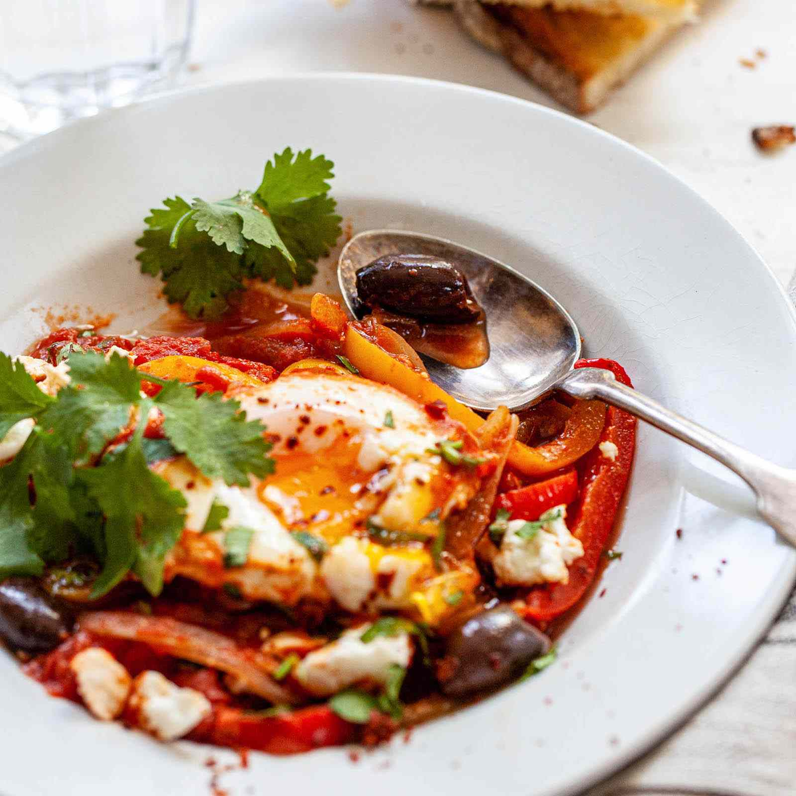 Easy Shakshuka in a bowl with a side of bread.