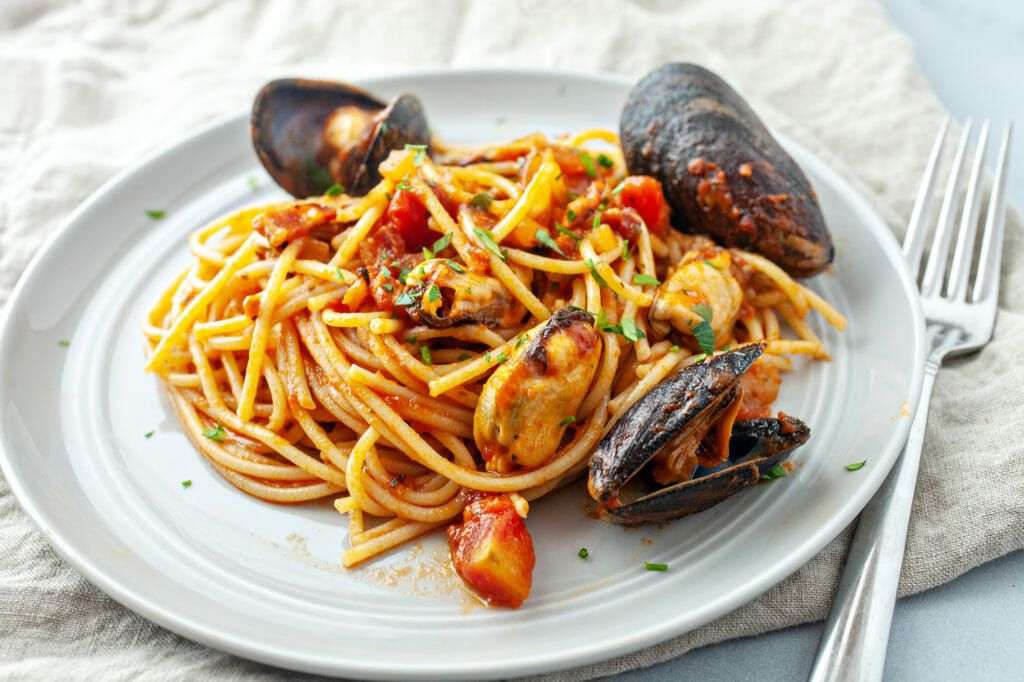 How to Cook Mussels in Tomato Sauce - spaghetti with sauce and mussels on plate