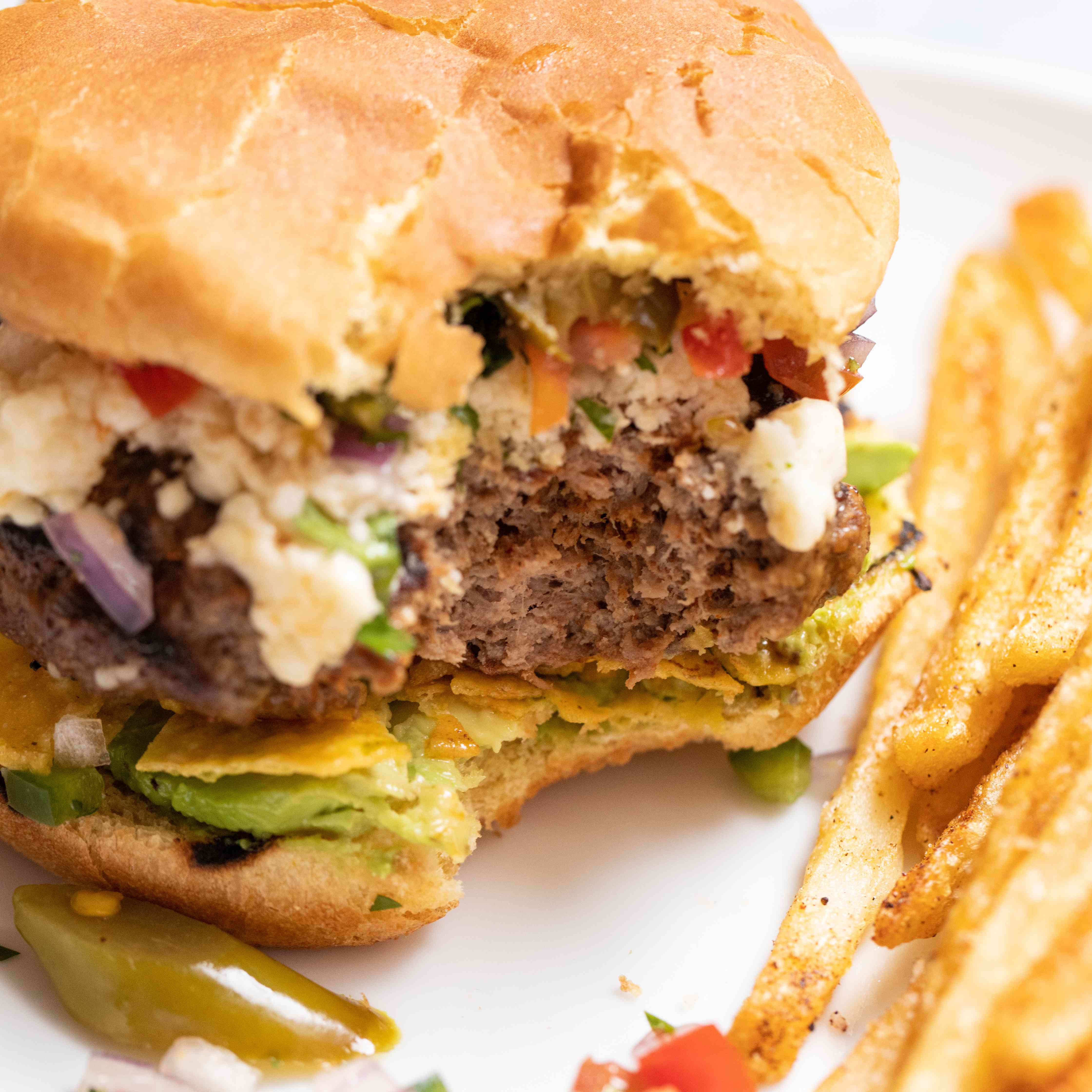 Mexican burger on a plate with a bite taken out and fries on the side.