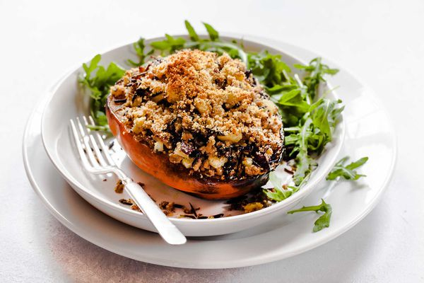 Stuffed Squash with Turkey, Apples and Rice is in a bowl, ontop of a plate with a fork on the side.