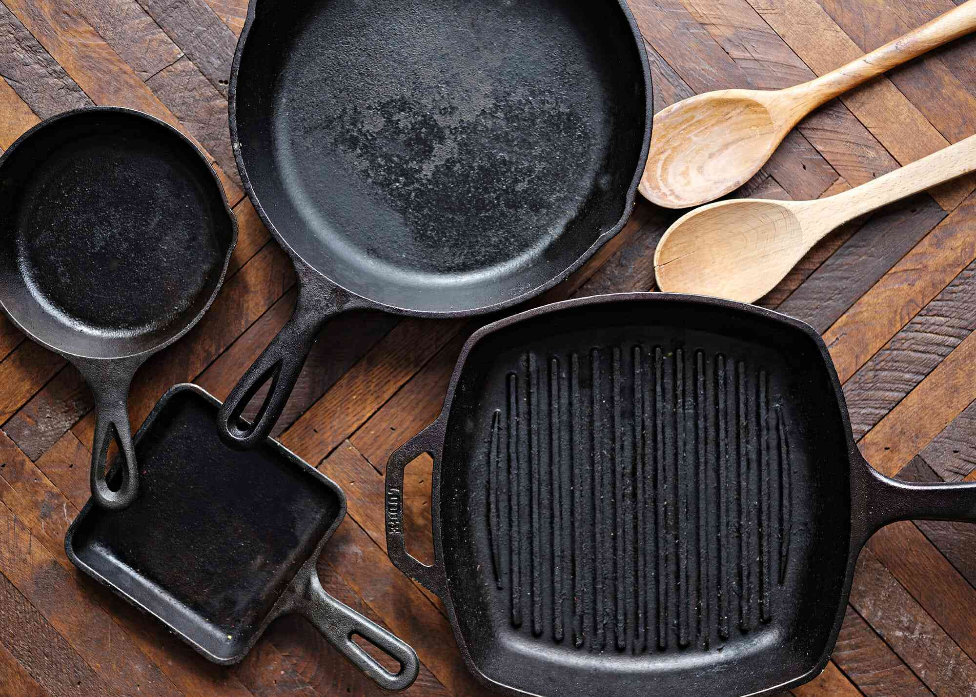 How to Season a Cast Iron Pan - cast iron skillets on a wooden table with wooden spoons nearby