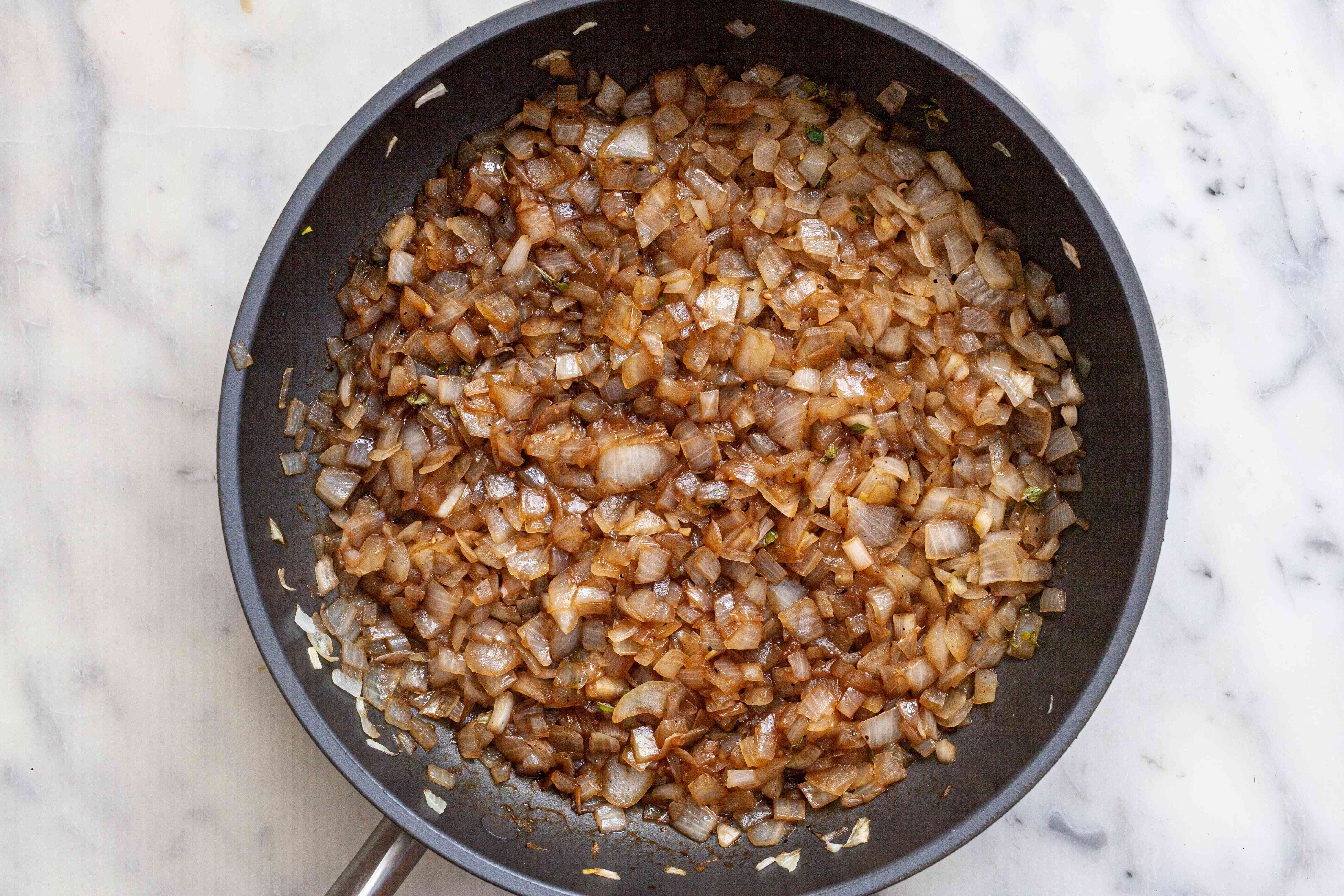 Sauteed onions in a skillet to make an Onion jam recipe with balsamic vinegar.