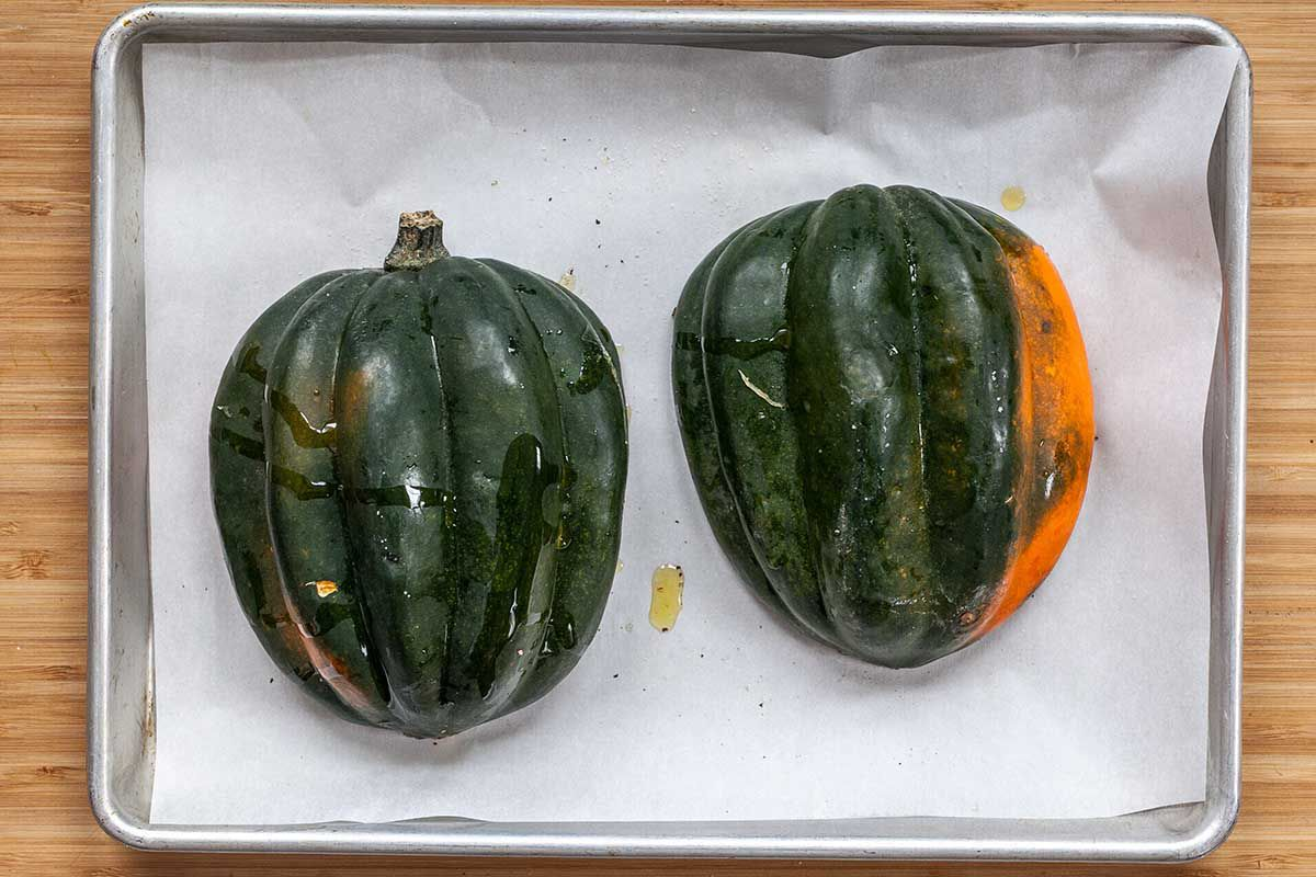 Acorn Squash sliced in half on a sheet of parchment. The sliced half is facing down.