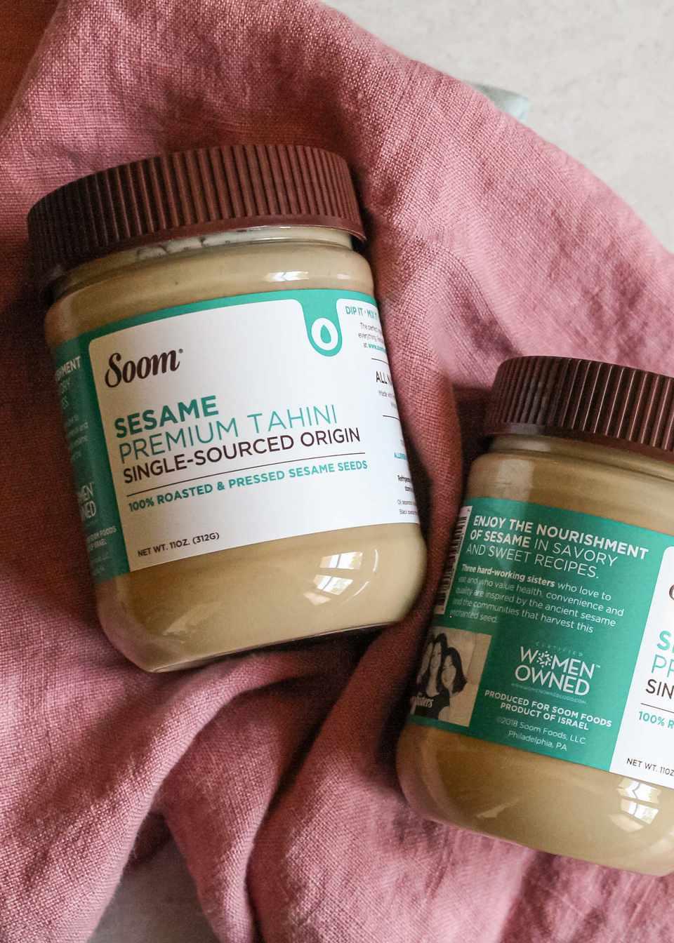 Two jars of Soom tahini on a pink linen.